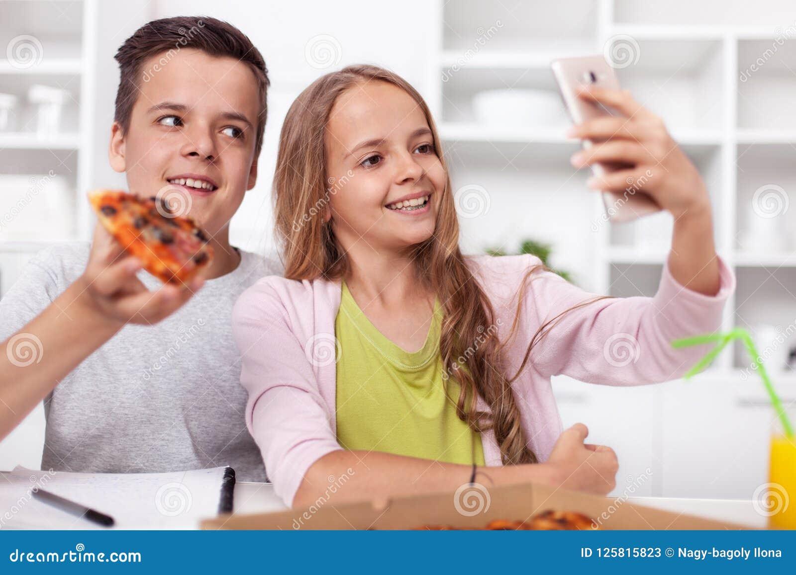 Młoda nastolatek chłopiec, dziewczyna bierze selfie i - łasowanie pizza