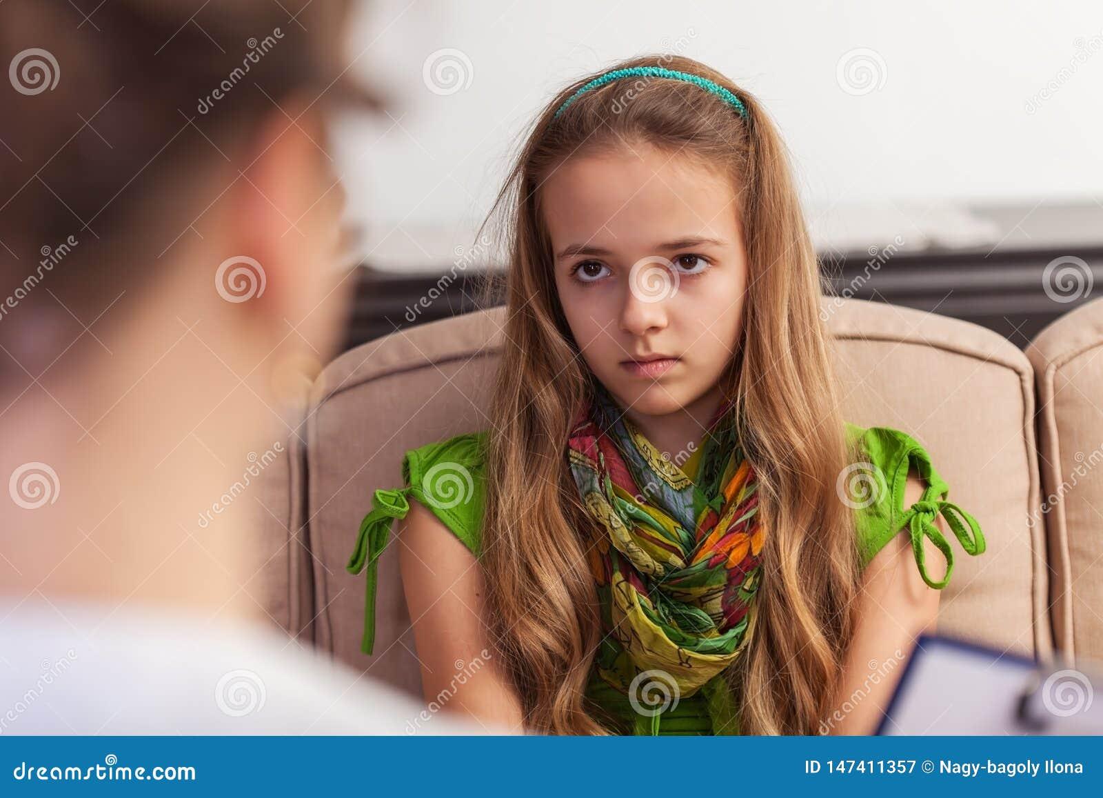 Młoda nastolatek dziewczyna patrzeje z niewiarą i zanudzająca, siedzący przy doradzać