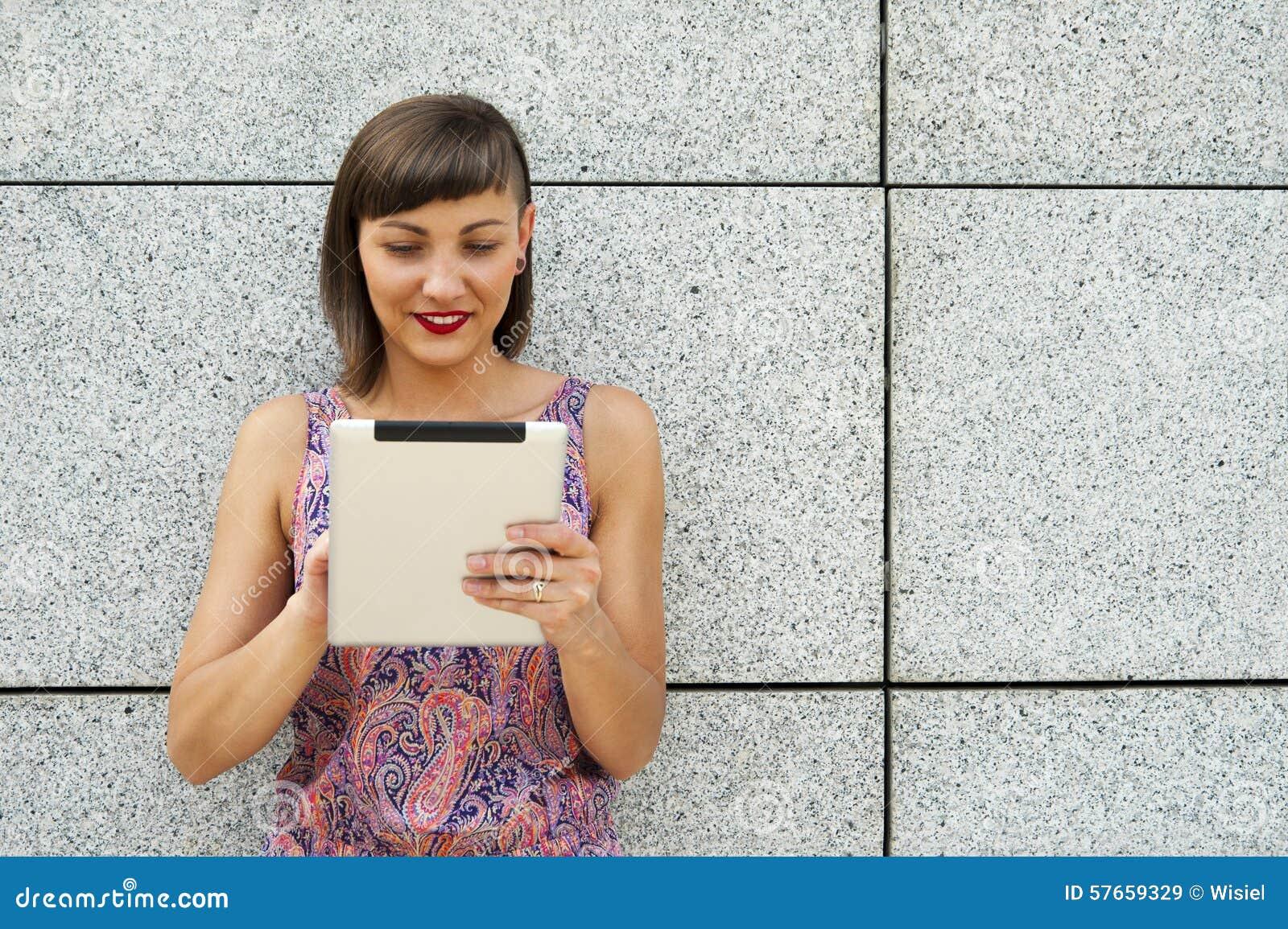 Młoda nowożytna kobieta używa pastylkę w mieście ścianą, ono uśmiecha się