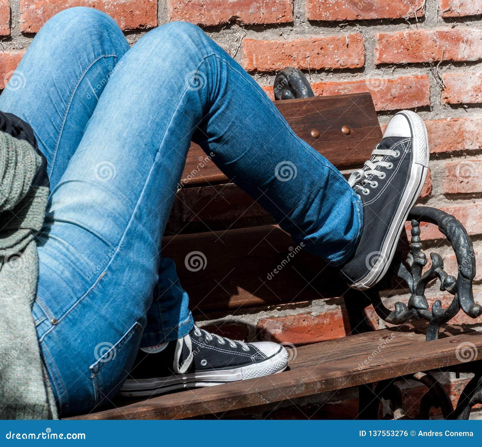 Młoda osoba z niebieskich dżinsów i sneakers łgarskim puszkiem na drewnianej ławce z czerwonych cegieł tłem