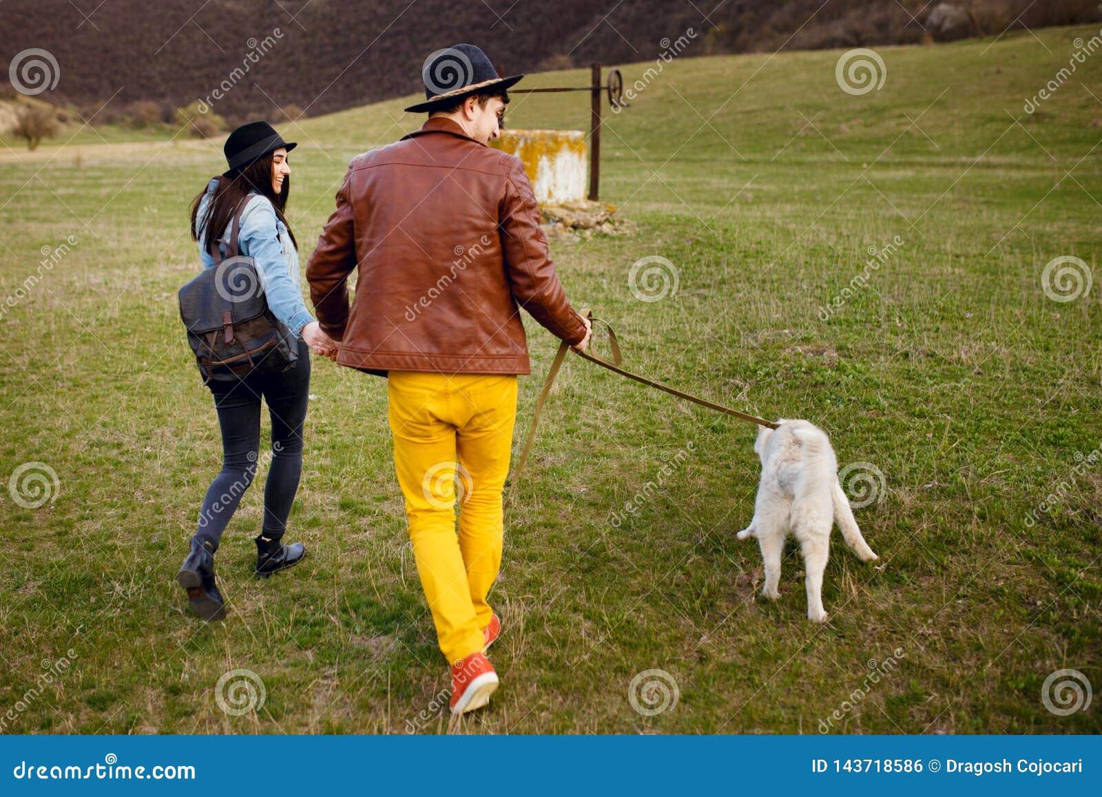Młoda para wydaje czas outside z ich łuskowatym psem wpólnie Romantyczny pojęcia styl życia