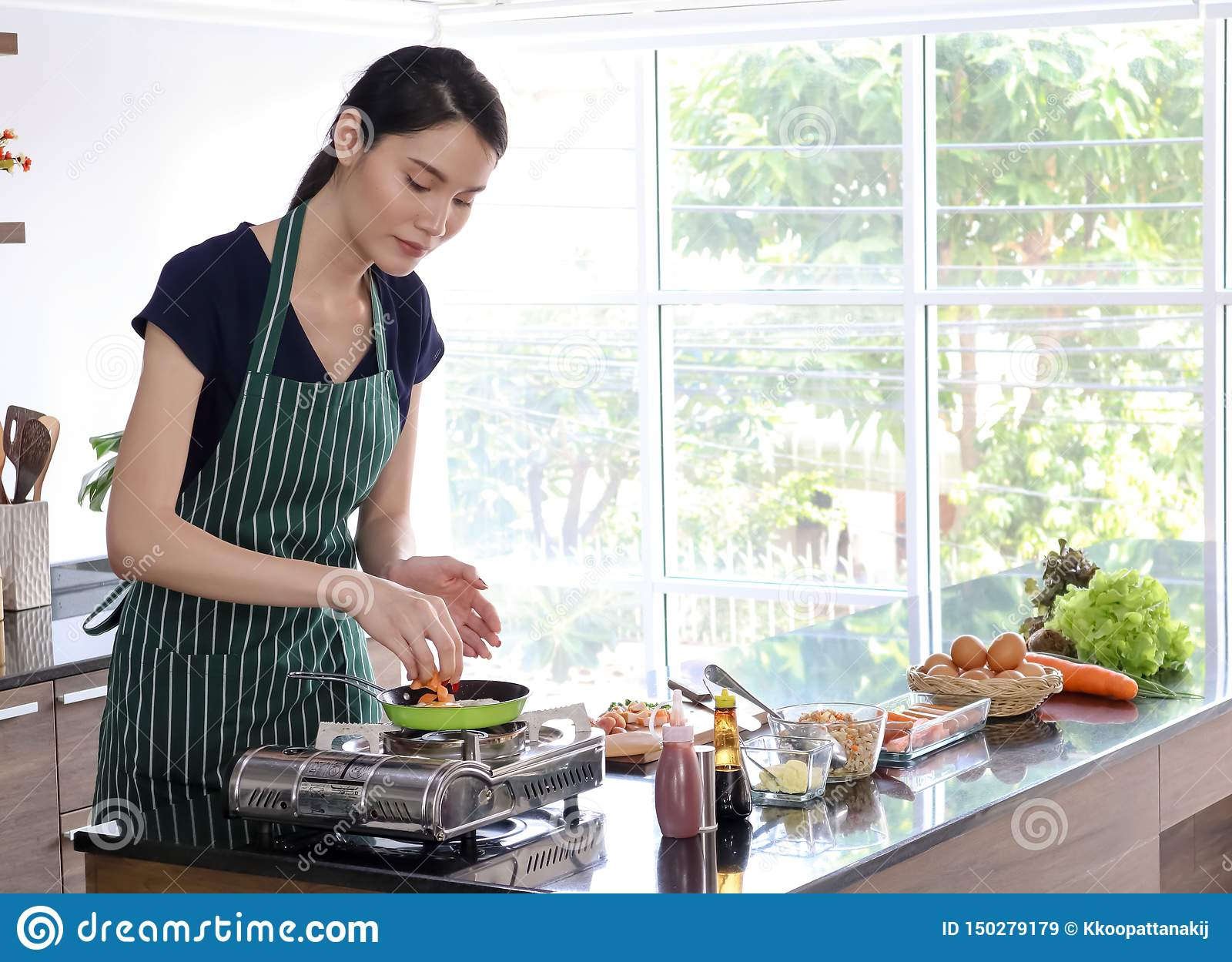 Młoda piękna Azjatycka kobieta z zielonymi lampasa fartucha kucharzami na niecce