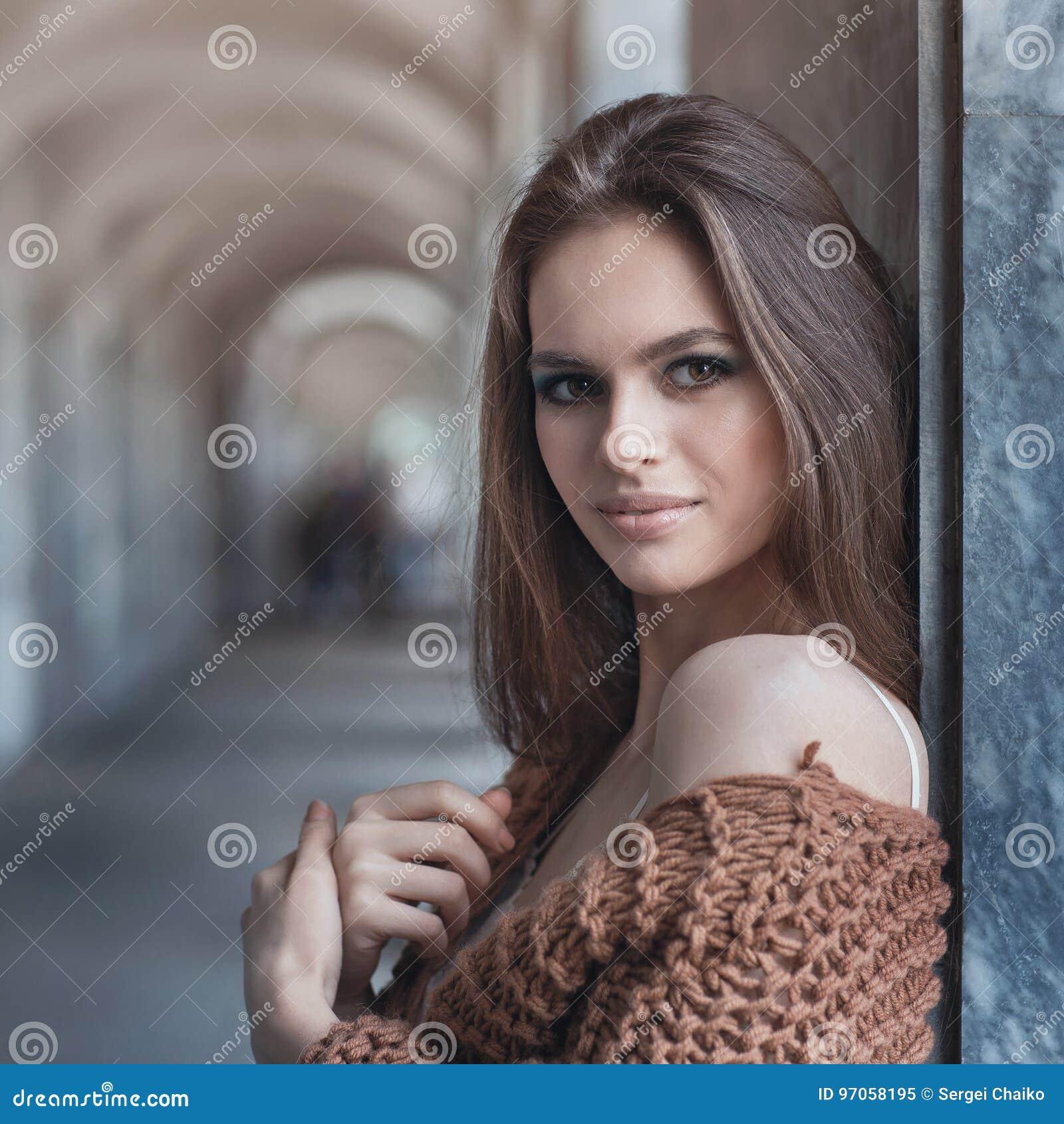 Młoda piękna brunetka w modnych ubraniach blisko ściany