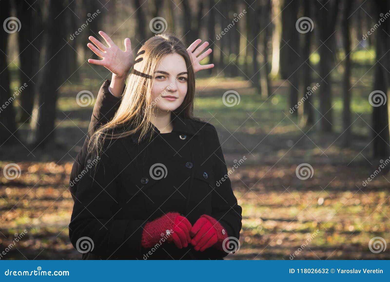 Młoda piękna dziewczyna bada wiosna lasu parka w czarnego żakieta czerwonych rękawiczkach