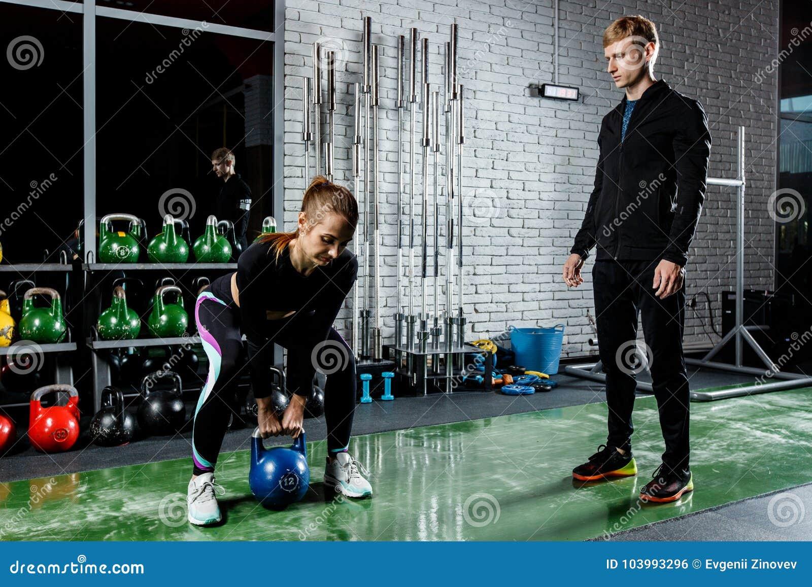 Młoda piękna dziewczyna robi ćwiczeniu z ciężarami pod kierownictwem trenera