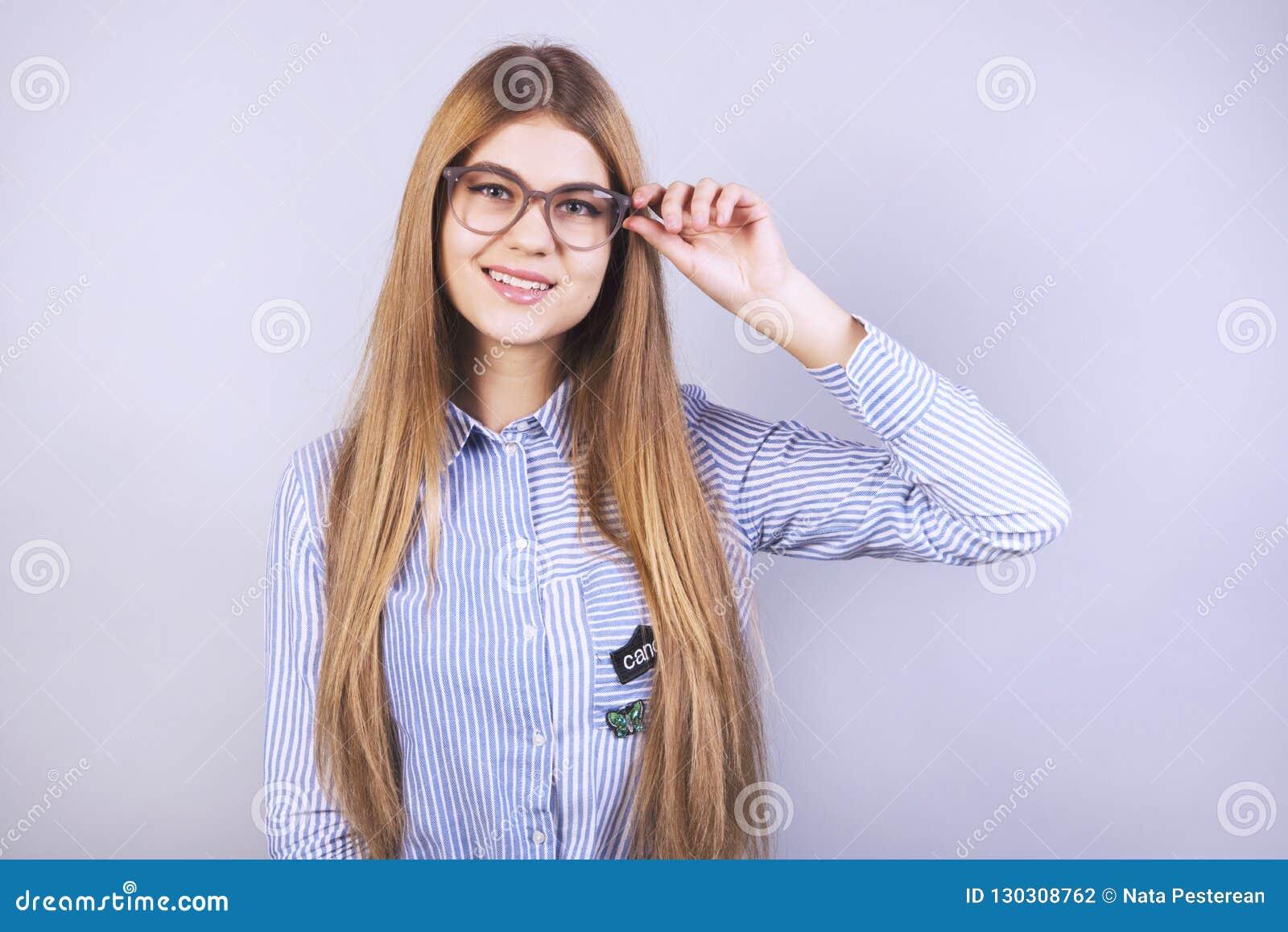 Młoda piękna dziewczyna stoi przed popielatym tłem, uśmiecha się koszula i jest ubranym z szkłami, mnóstwo czysty