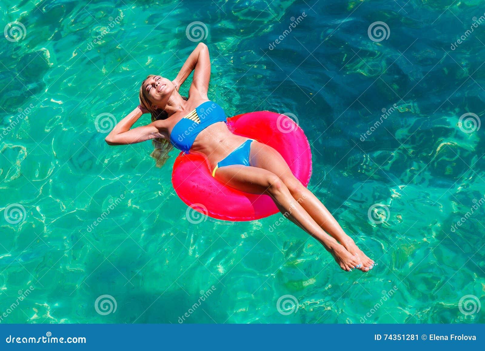 Młoda piękna dziewczyna w bikini pływa w tropikalnym morzu na rubb