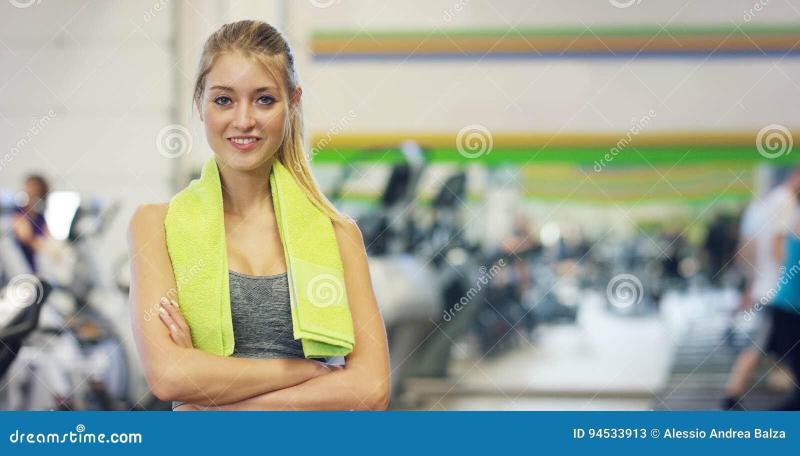 Młoda piękna dziewczyna w gym, stojaki ono uśmiecha się z ręcznikiem na jej ramieniu po trenowania i relaksującym Pojęcie: kochać