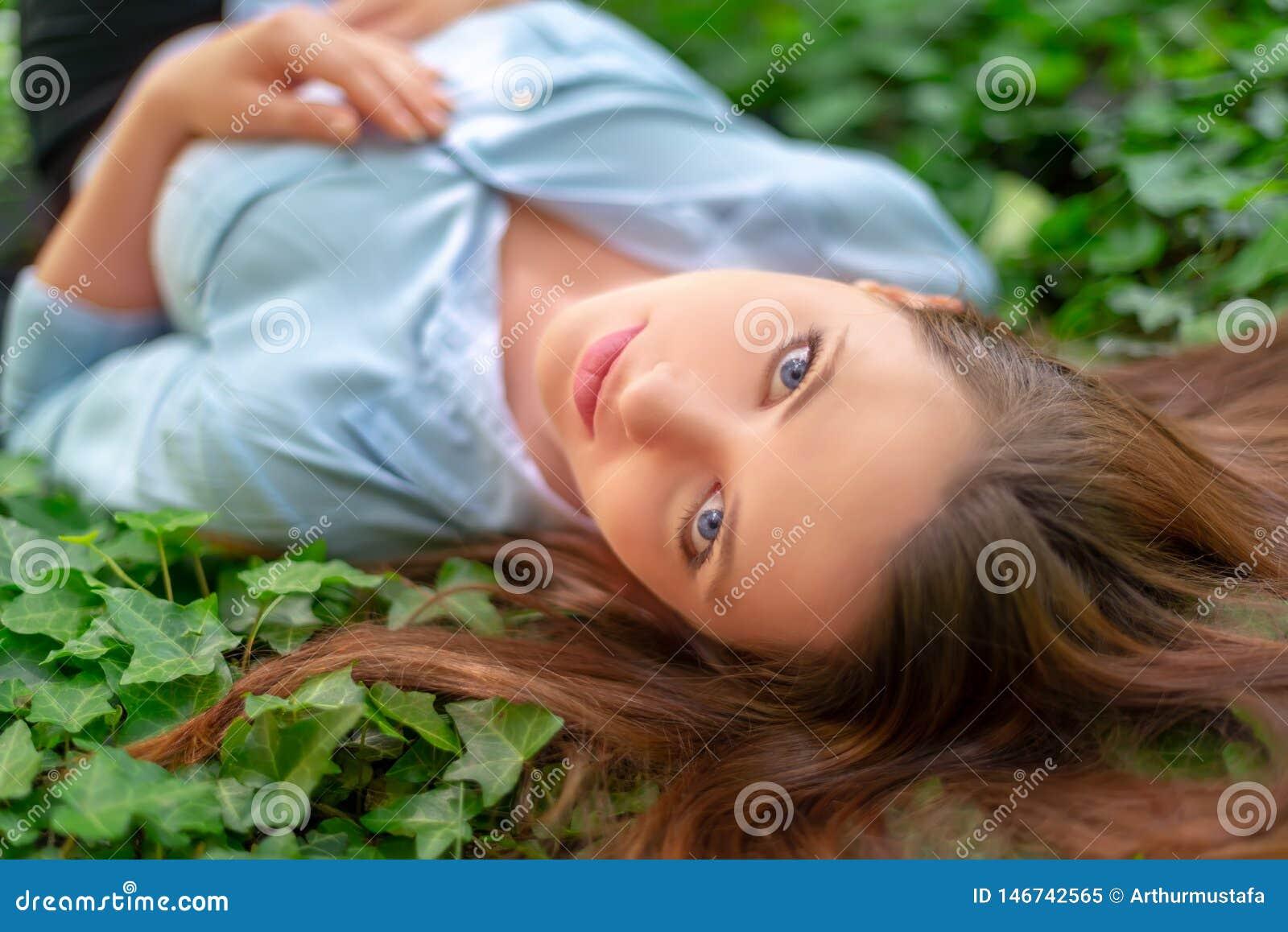 Młoda piękna dziewczyna z doskonalić skórą i makeup jest łgarskim puszkiem na bluszcz łące w wiosna parka scenerii, patrzeje