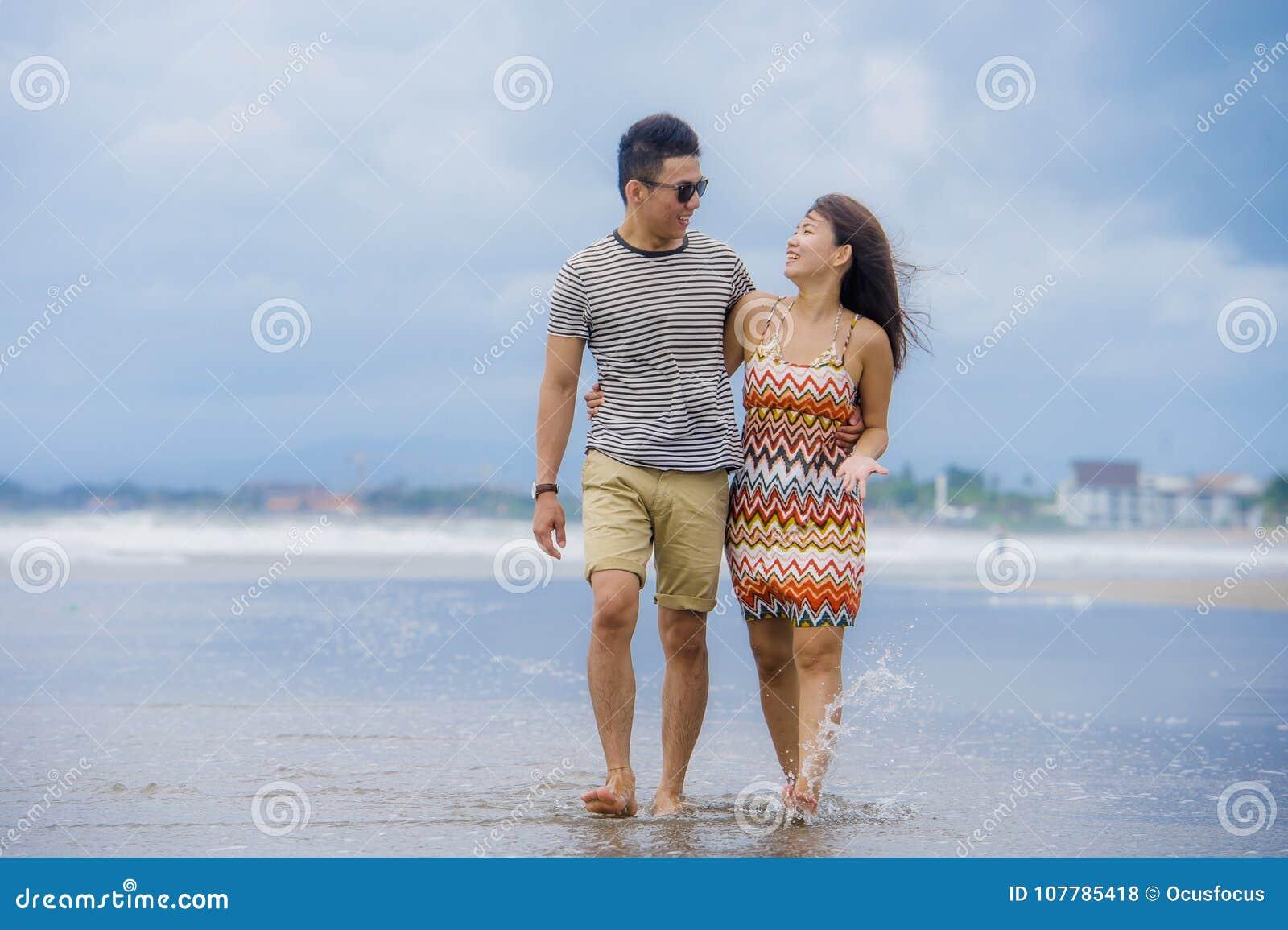 Młoda piękna i Azjatycka Chińska romantyczna para chodzi wpólnie obejmować na plaży szczęśliwej w miłości cieszy się wakacje