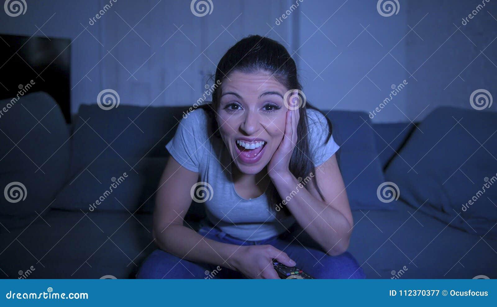 Młoda piękna i szczęśliwa łacińska kobieta trzyma TV pilota cieszy się w domu na jej 30s żyjący izbowego leżanki dopatrywania pro