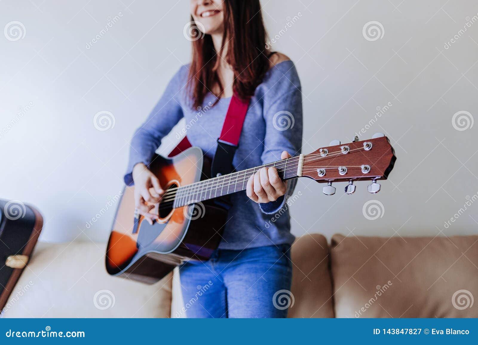 Młoda piękna kobieta bawić się gitary pozycję na kanapie pojęcia gitary elektrycznej ilustraci muzyka