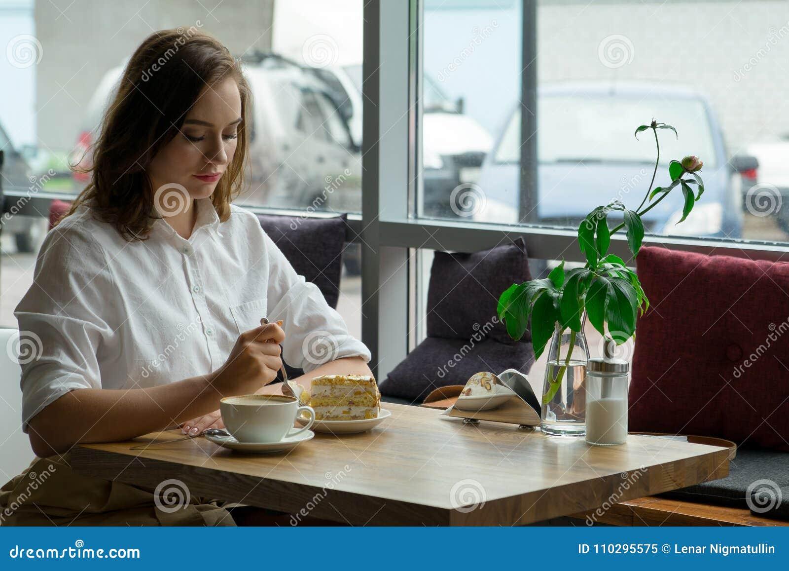 Młoda piękna kobieta pije kawę w kawiarni młoda kobieta w biznesie odziewa na przerwa na lunch