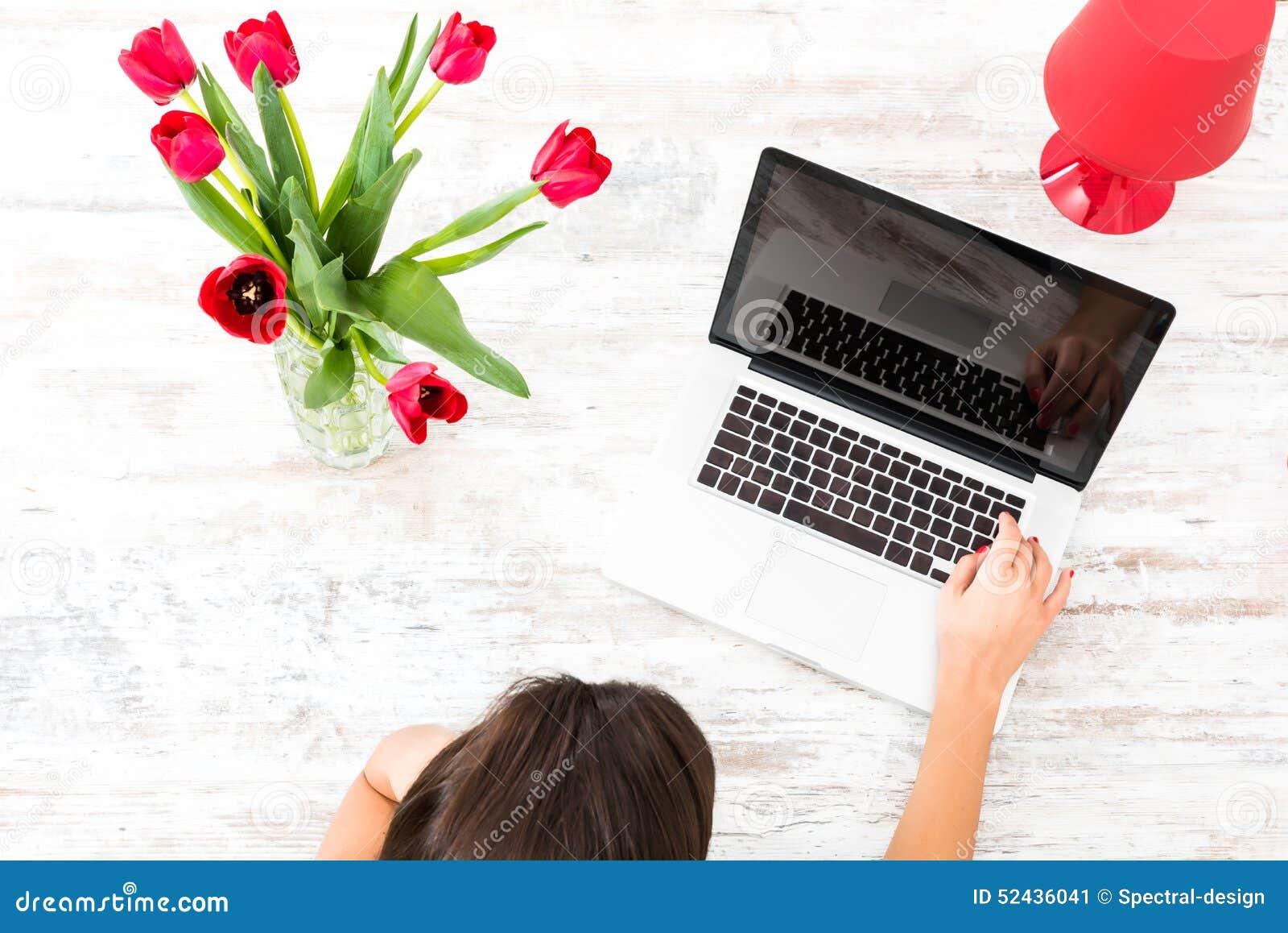 Młoda piękna kobieta używa laptop w domu