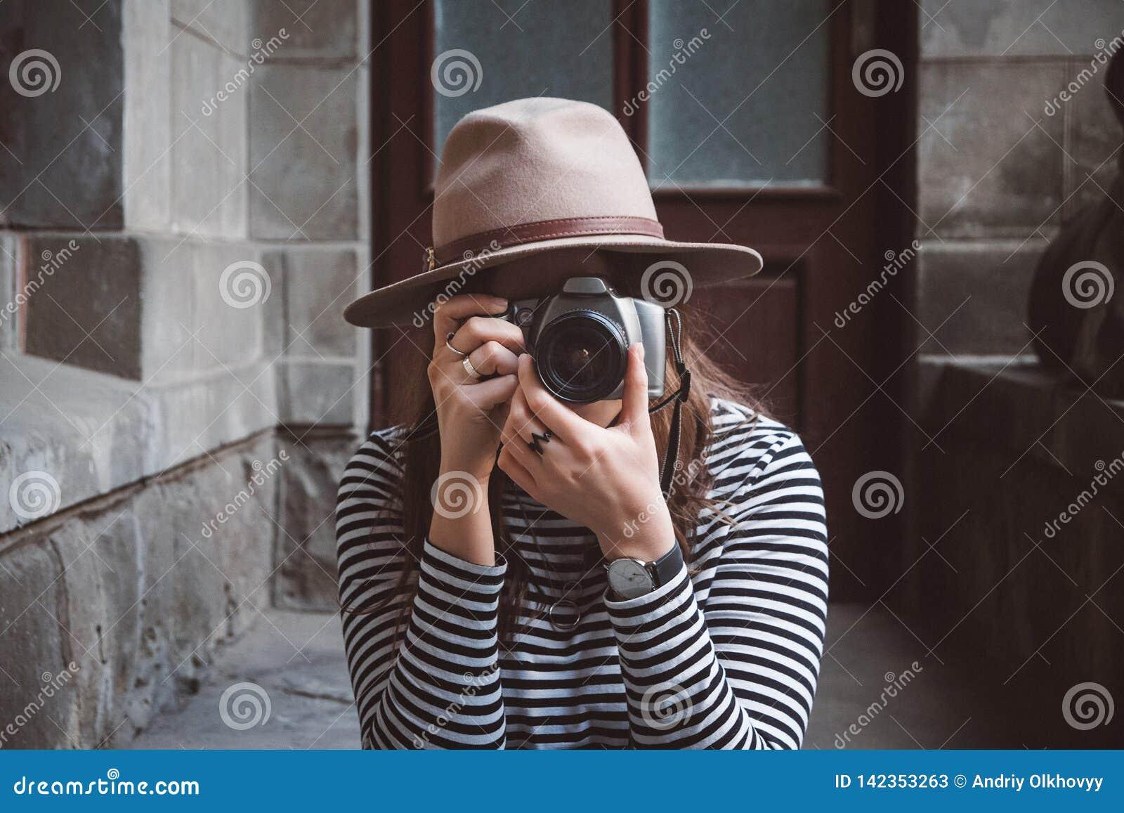 Młoda piękna kobieta w kapeluszu bierze obrazek z staromodną kamerą, outdoors