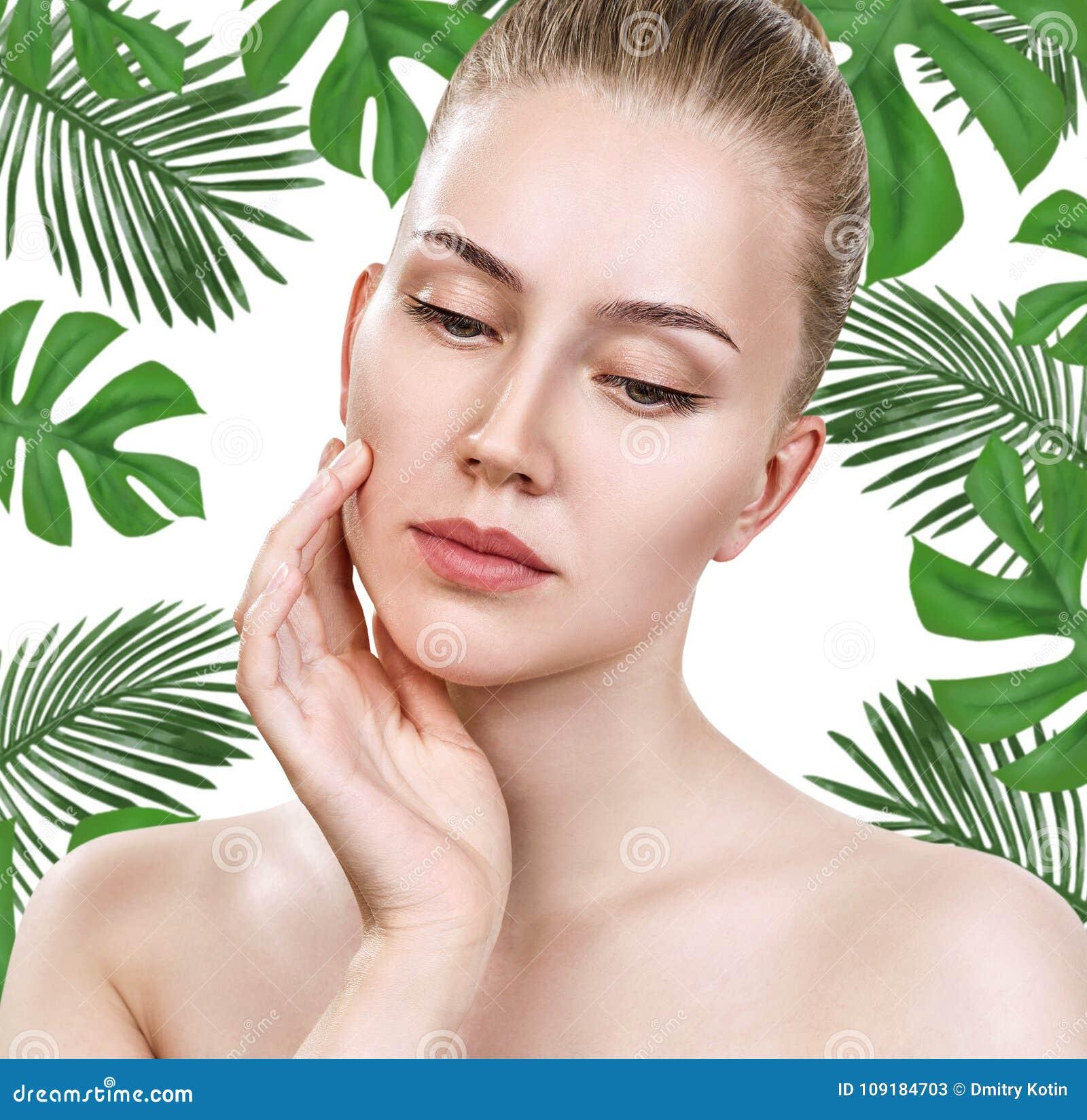 Młoda piękna kobiety twarz wśród zielonych palmowych liści