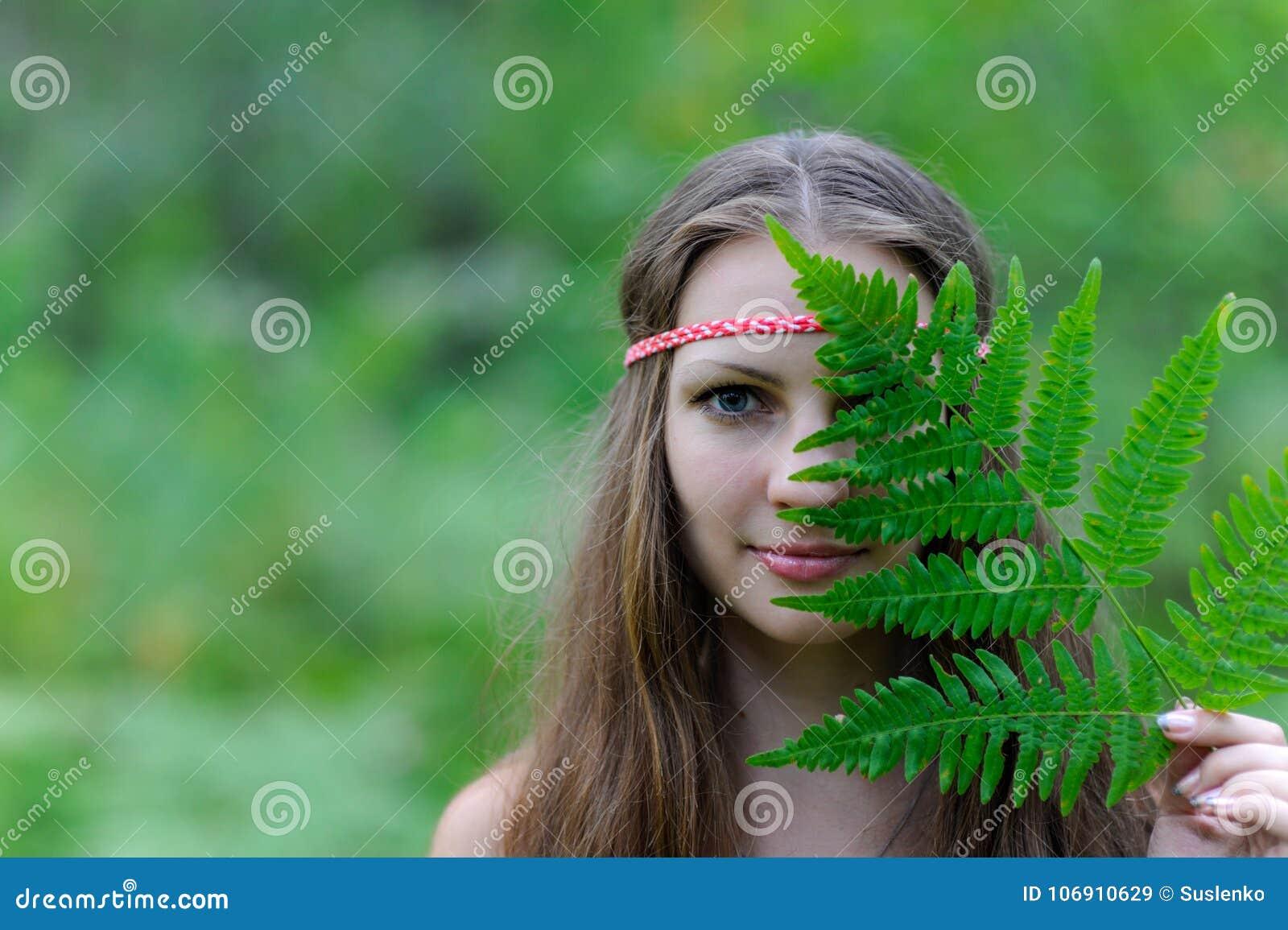 Młoda piękna Slawistyczna dziewczyna z długie włosy i Slawistyczną etniczną suknią zakrywał jej twarz z paprociowym liściem