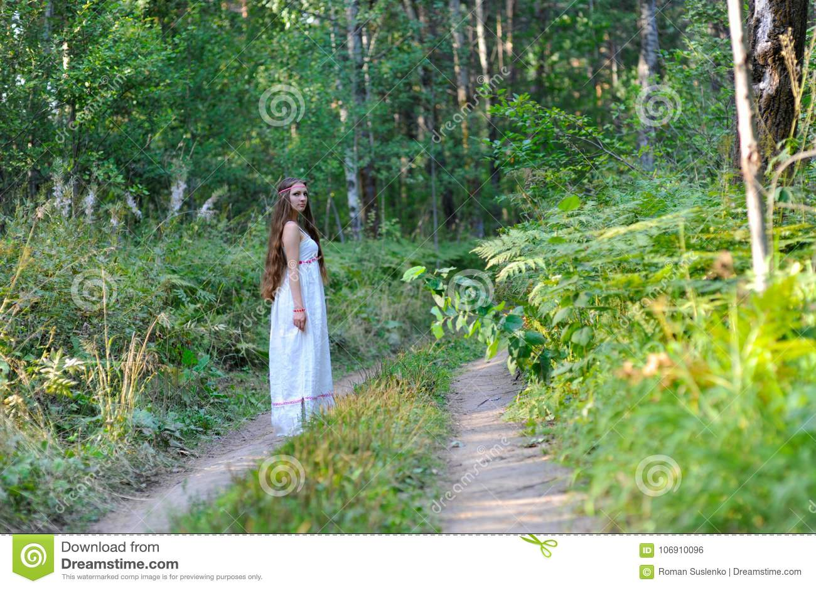 Młoda piękna Slawistyczna dziewczyna z długie włosy i Slawistycznym etnicznym ubioru odprowadzeniem wzdłuż śladu w lato lesie