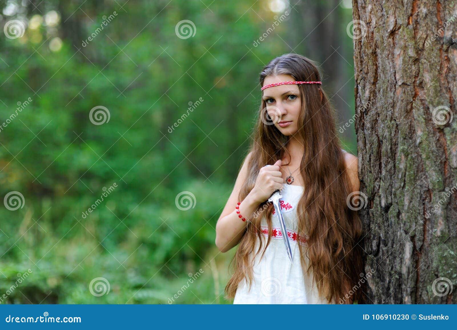 Młoda piękna Slawistyczna dziewczyna z długie włosy i Slawistycznymi etnicznymi suknia stojakami w lato lesie z obrządkowym kindż