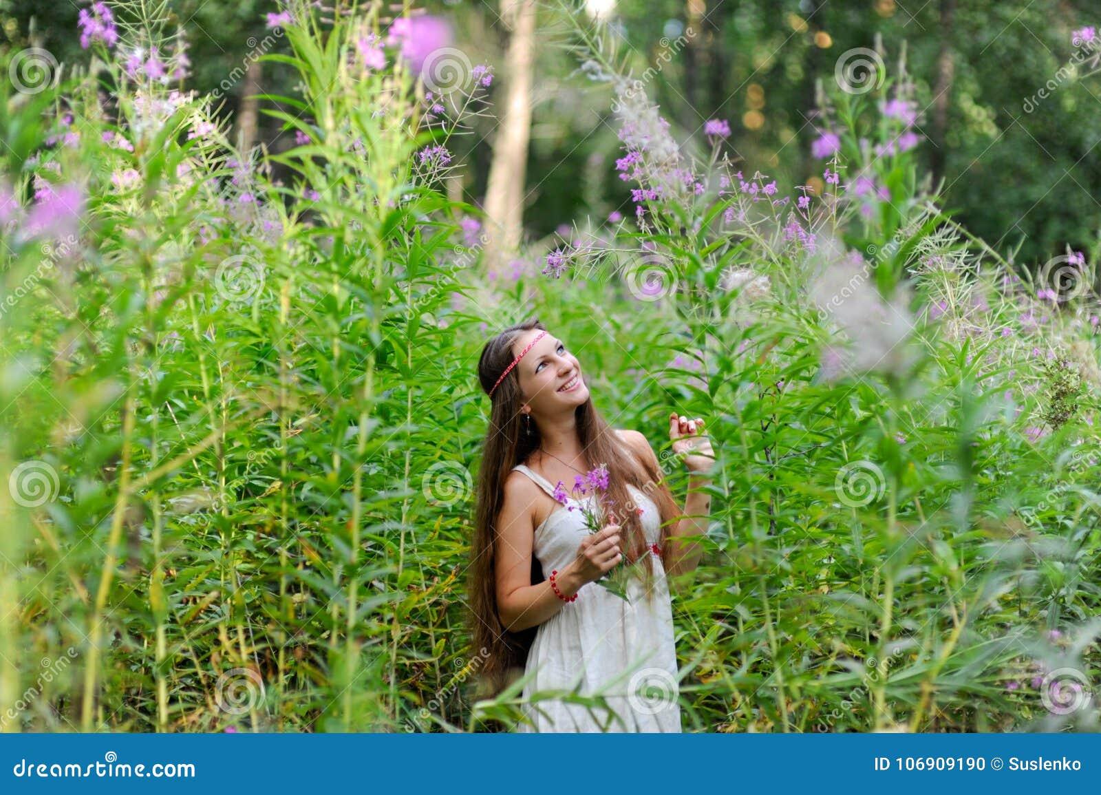 Młoda piękna Slawistyczna dziewczyna z długie włosy i sukni Slawistyczni etniczni stojaki wśród wysokiego porośla w lato lesie i