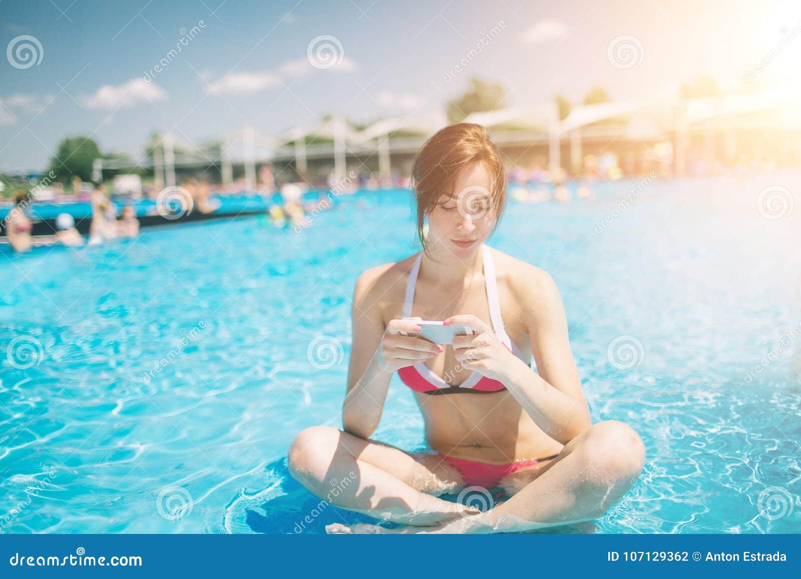 Młoda piękna uśmiechnięta kobieta w bikini w ciepłym basenie na kurorcie i rozmowie w telefonie komórkowym