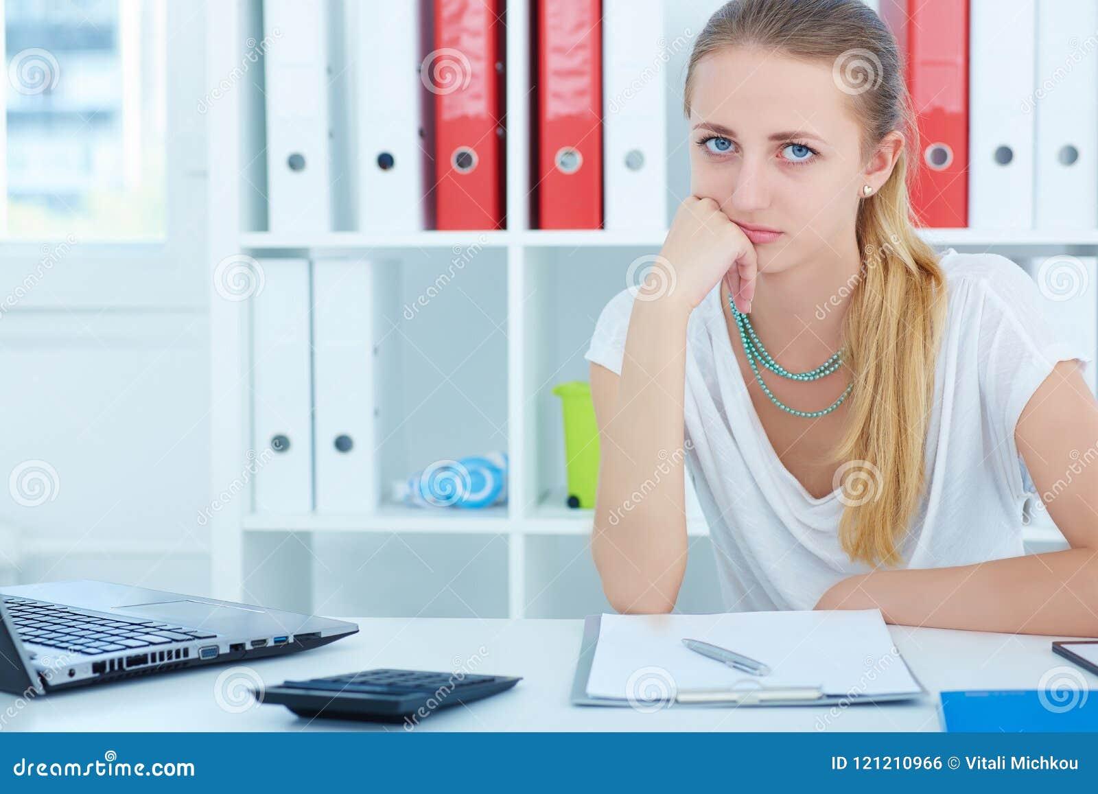Młoda piękna zmęczona dziewczyna siedzi podpierającą głowę w jego rękach i patrzeć kamerę przy biurkiem w biurze