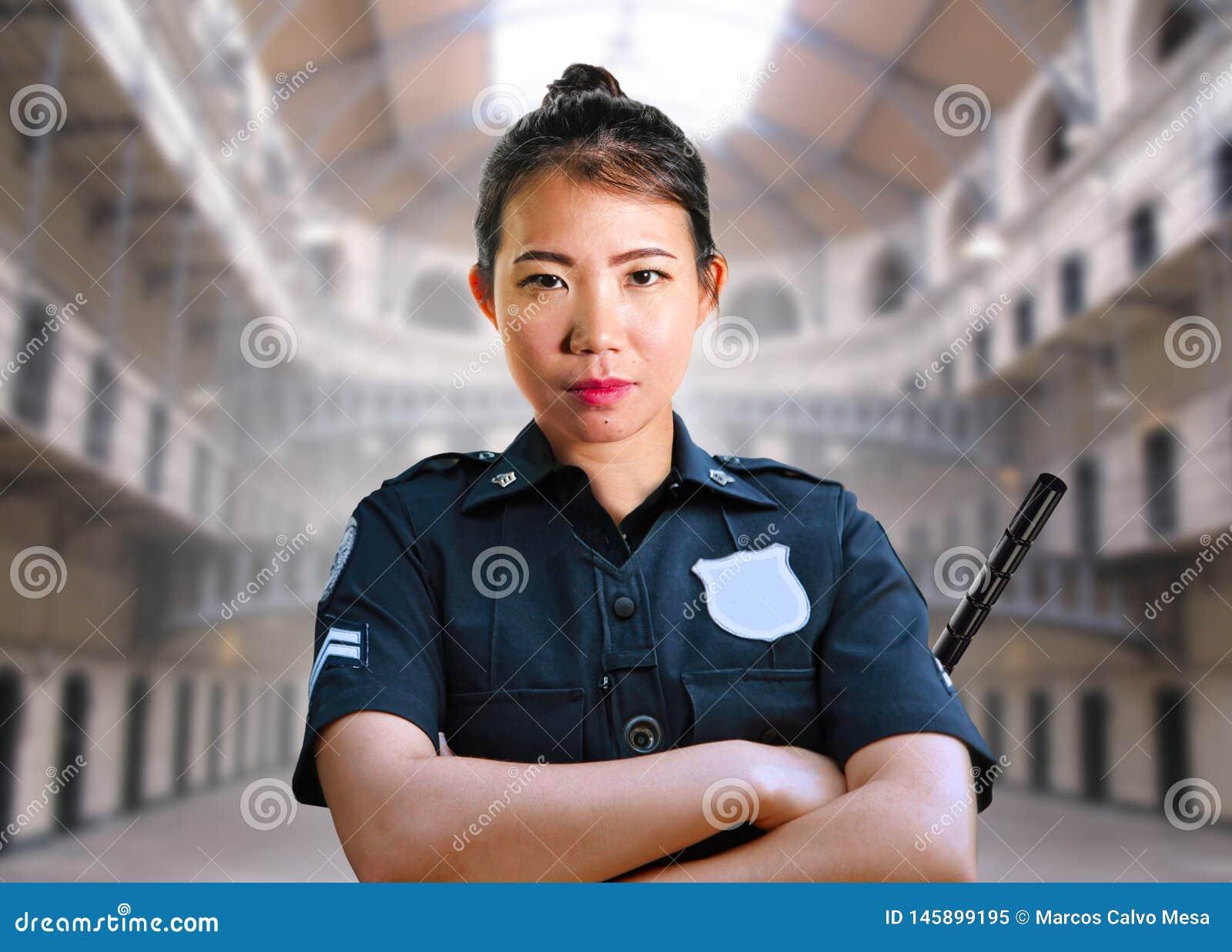 Młoda poważna i atrakcyjna Azjatycka amerykanina strażnika kobiety pozycja przy stan penitencjarną więźniarską salą jest ubranym