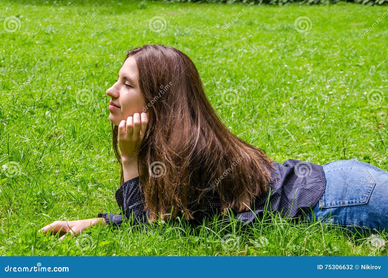 Młoda powabna dziewczyna nastolatek z długie włosy łgarskim puszkiem i odpoczywać na zielonej trawie podczas gdy chodzący w parku