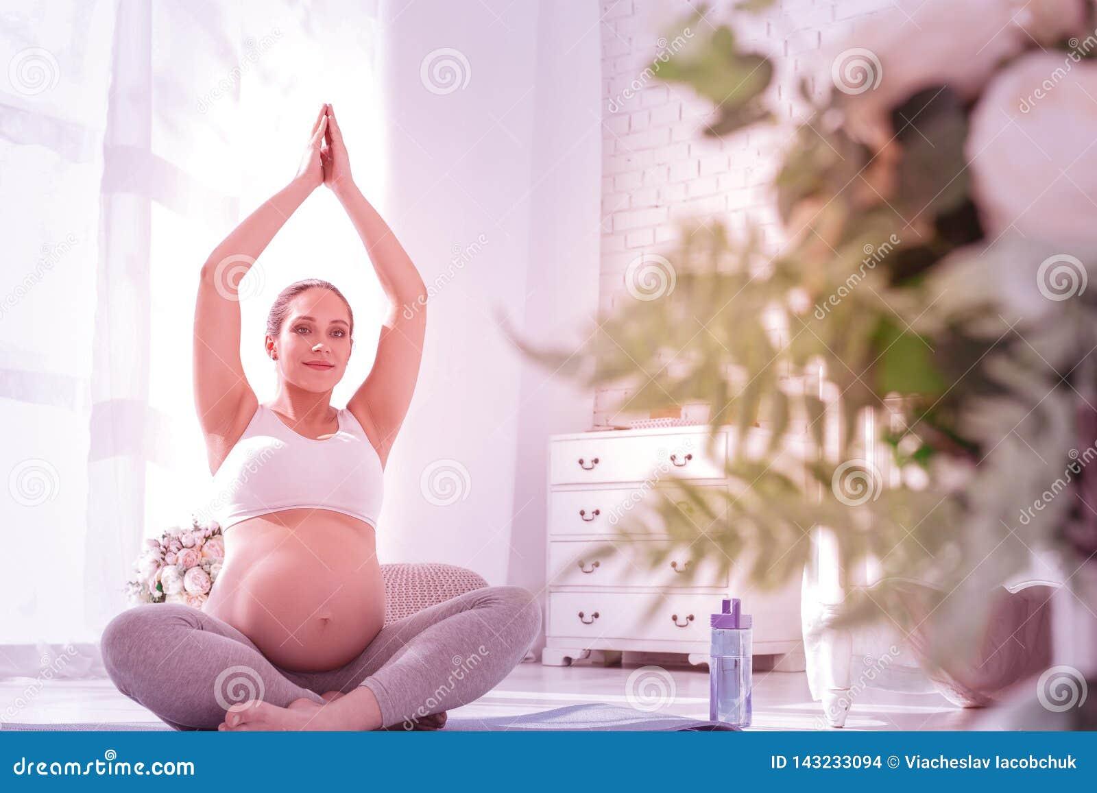 Młoda promieniejąca długowłosa kobieta w ciąży patrzeje pokojowy w białej koszulce