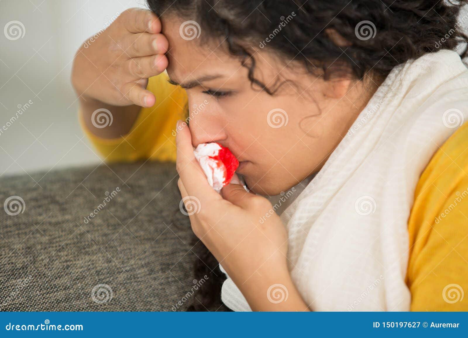 Młoda przestraszona kobieta z krwistym nosem