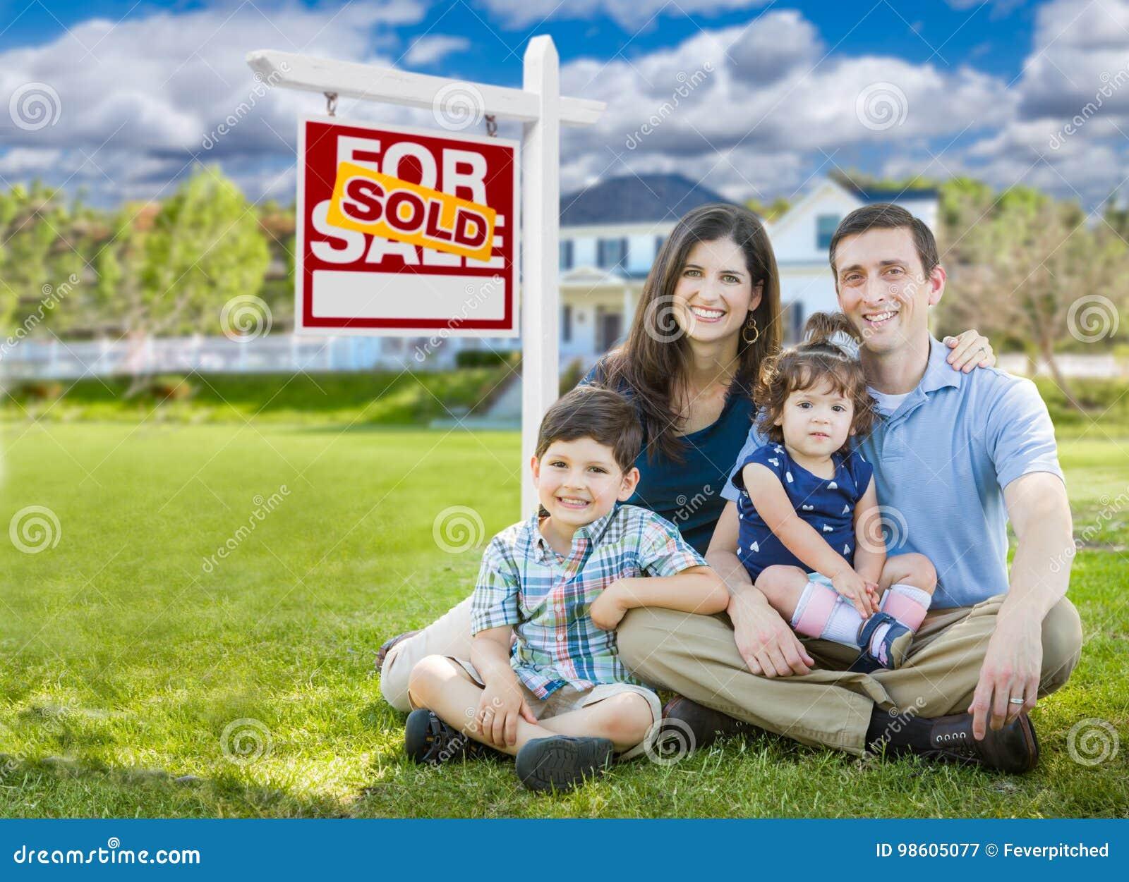 Młoda rodzina Z dzieciakami Przed zwyczaju domem i Sprzedającymi Dla sprzedaż znaka
