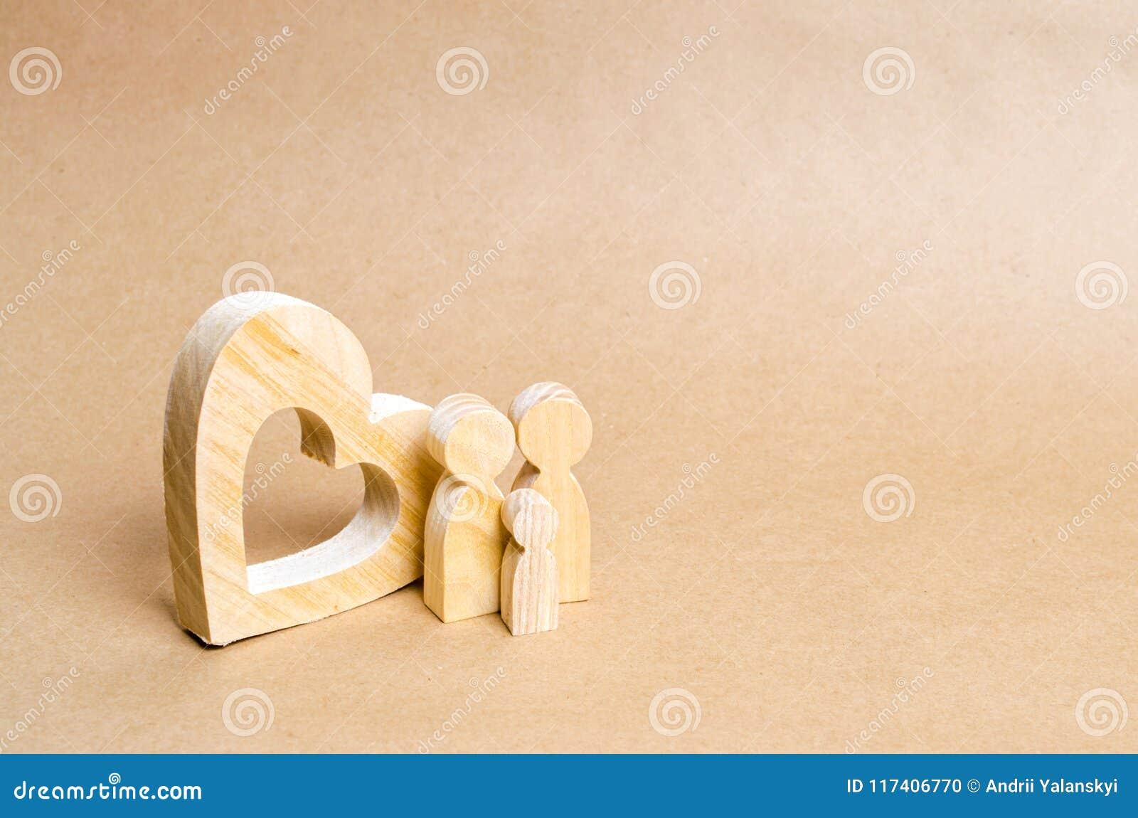 Młoda rodzina z dzieckiem stoi blisko drewnianego serca Miłość i lojalność, silna młoda rodzina Związki rodzinni
