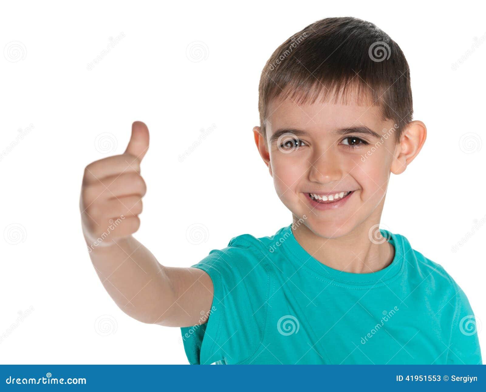 Młoda roześmiana chłopiec trzyma jego kciuk up