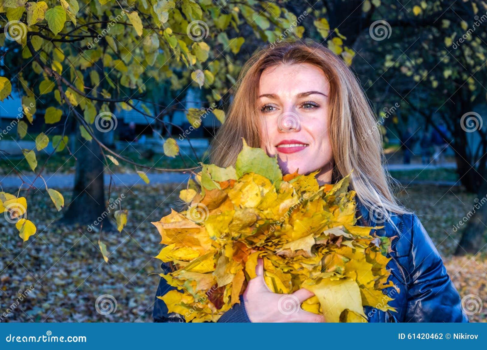 Młoda rozochocona śliczna dziewczyny kobieta bawić się z spadać jesień kolorem żółtym opuszcza w parku blisko drzewa, roześmiany