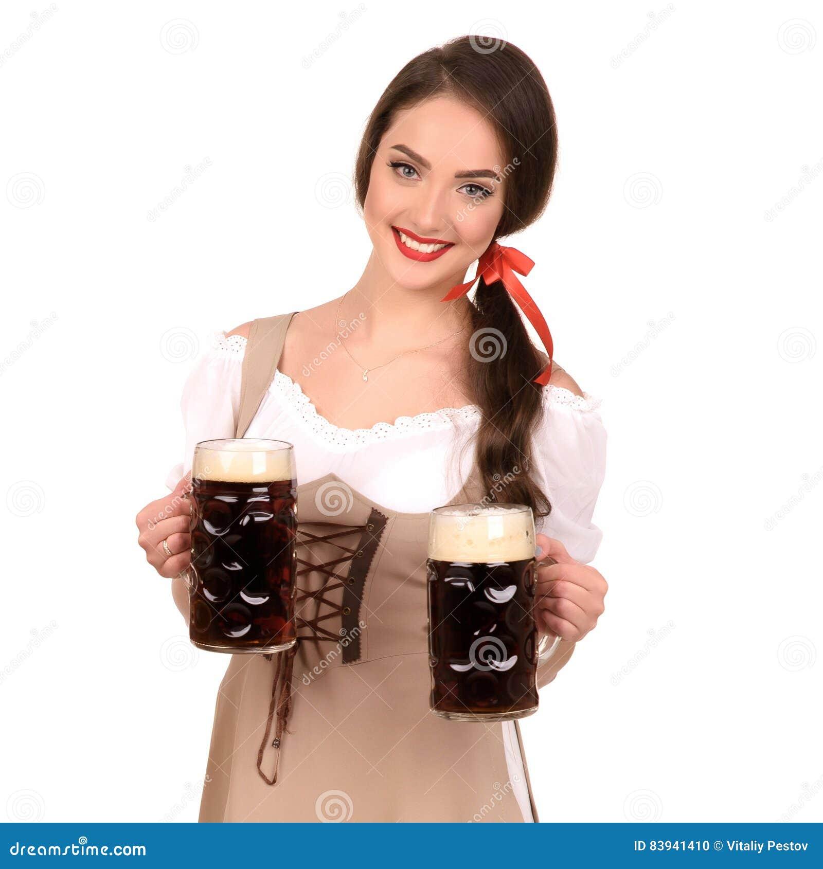Młoda seksowna kobieta jest ubranym dirndl z dwa piwnymi kubkami odizolowywa