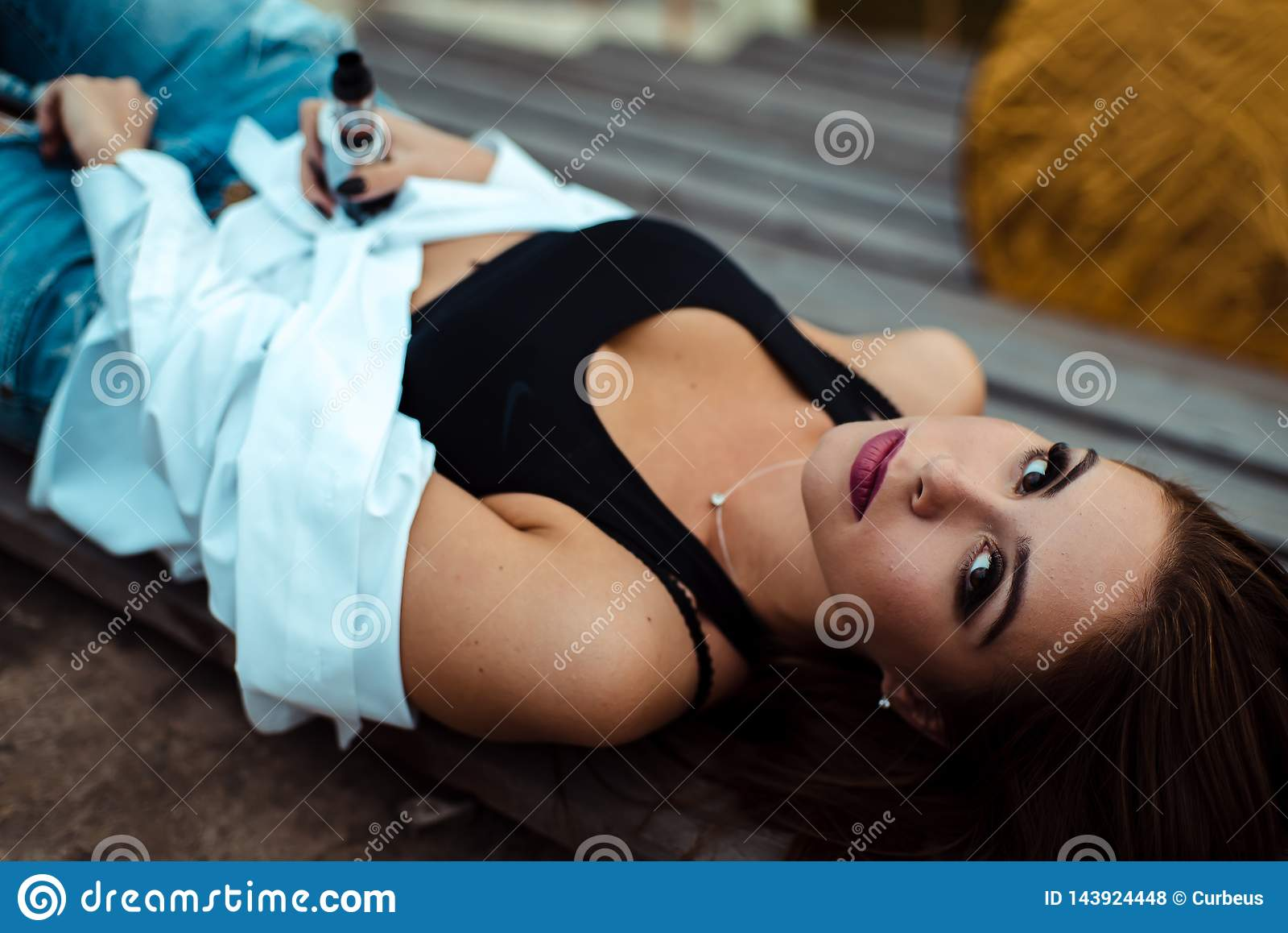 Młoda seksowna kobieta kłama na drewnianej ławce Bierze przerwę po treningu w gym plenerowy