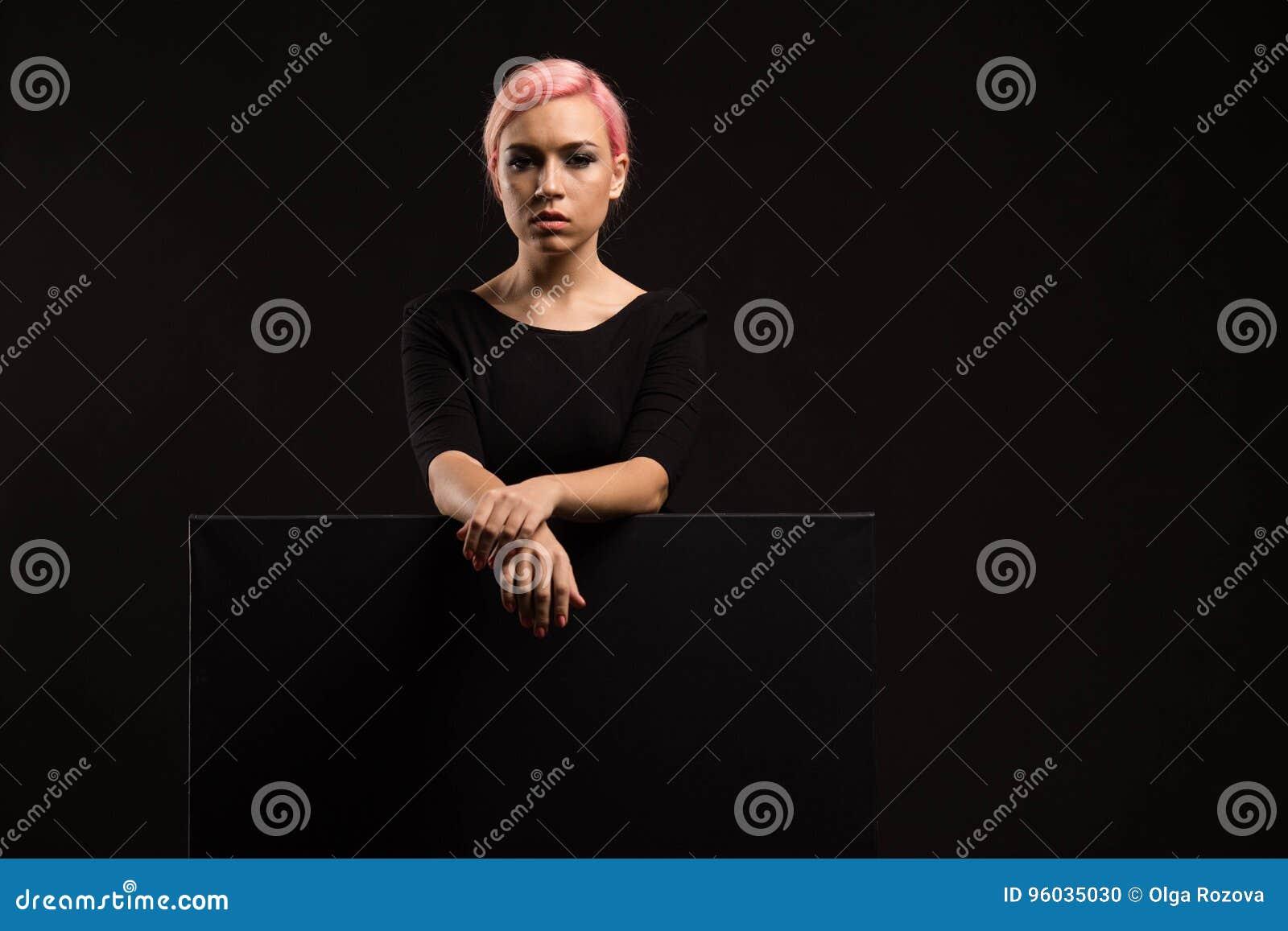 Młoda seksowna kobieta pokazuje prezentację, wskazuje na plakacie