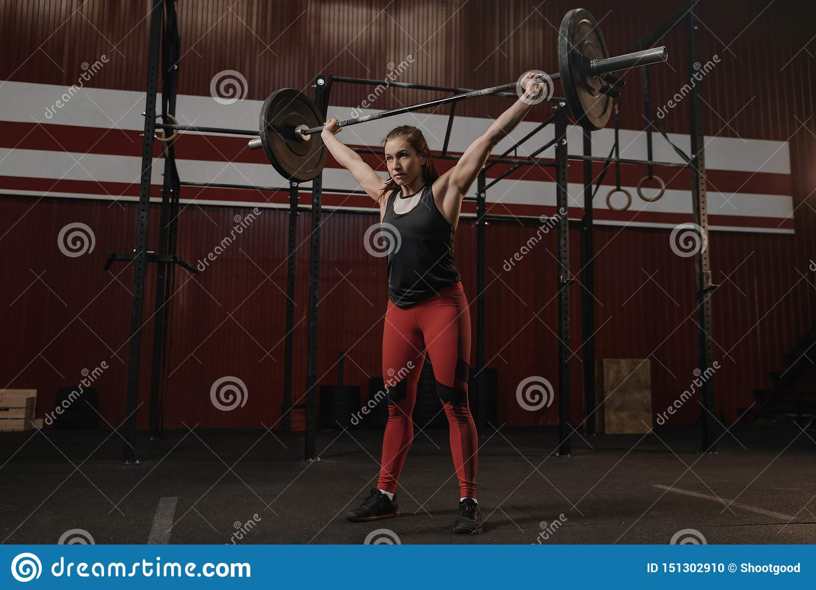Młoda silna kobieta trzyma ciężkiego barbell zasięrzutny Sport kobieta robi crossfit ćwiczeniu