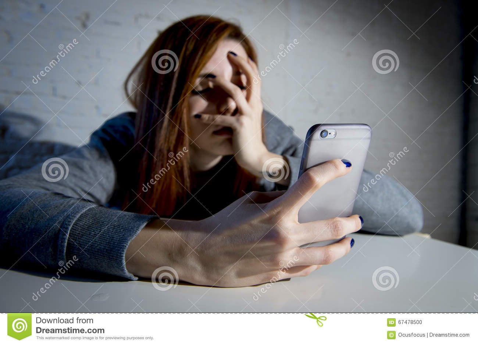 Młoda smutna podatna dziewczyna używa telefon komórkowego i desperackiego cierpienia online nadużycie cyberbullying okaleczał