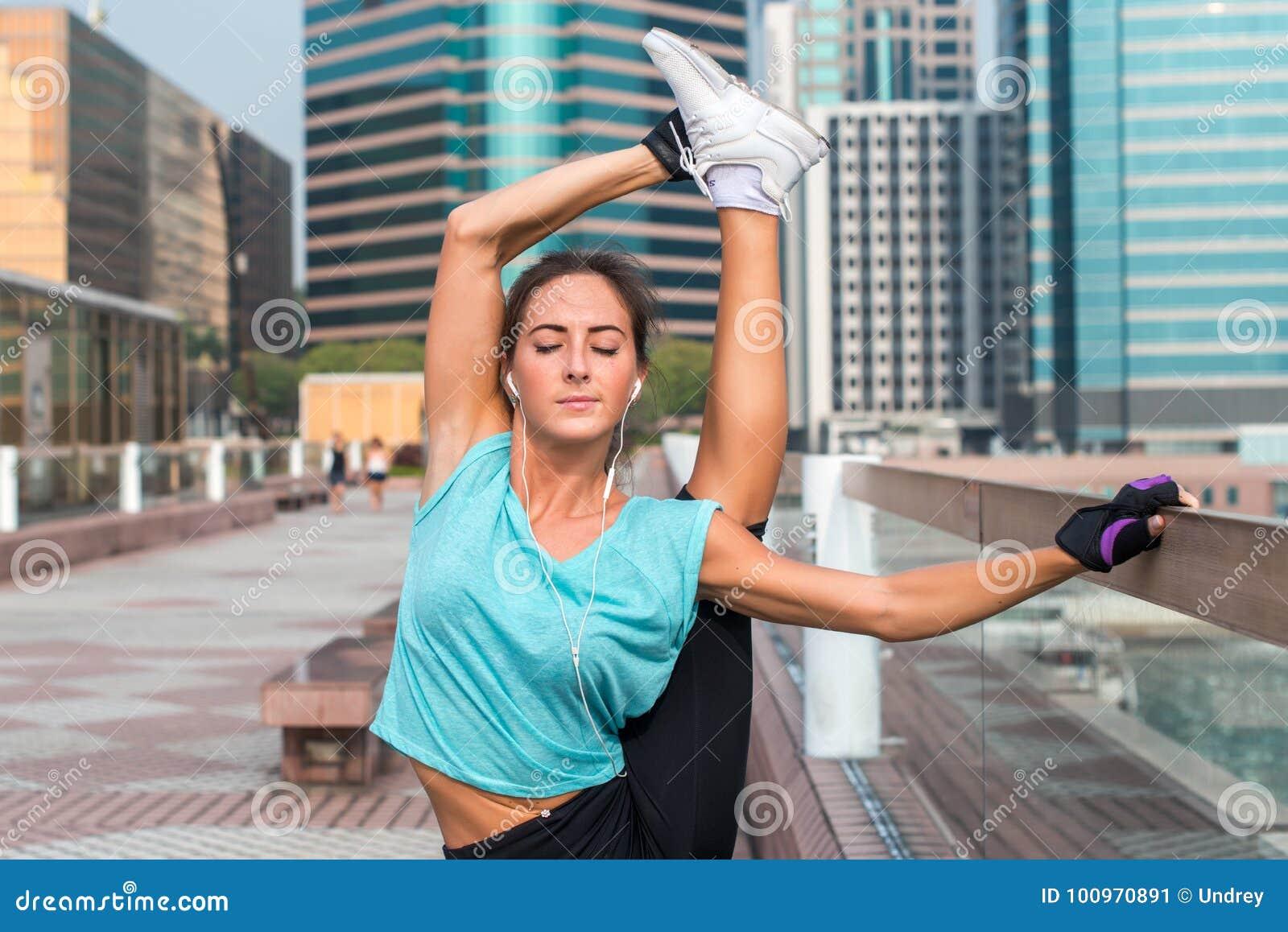 Młoda sprawności fizycznej kobieta robi stojący rozszczepionego ćwiczenie na miasto ulicie Sporty dysponowanej dziewczyny pracują