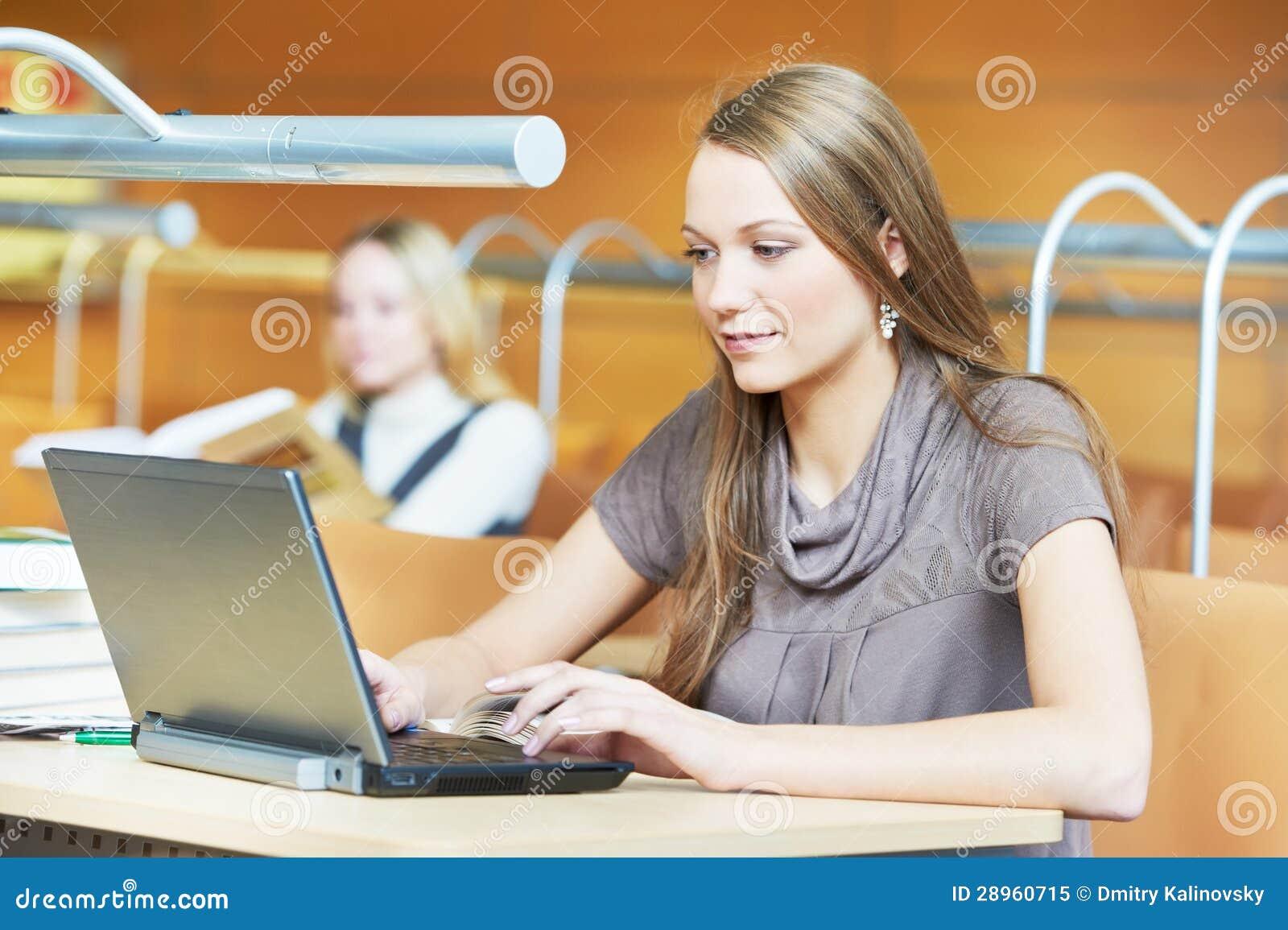 Młoda studencka dziewczyna pracuje z laptopem w bibliotece