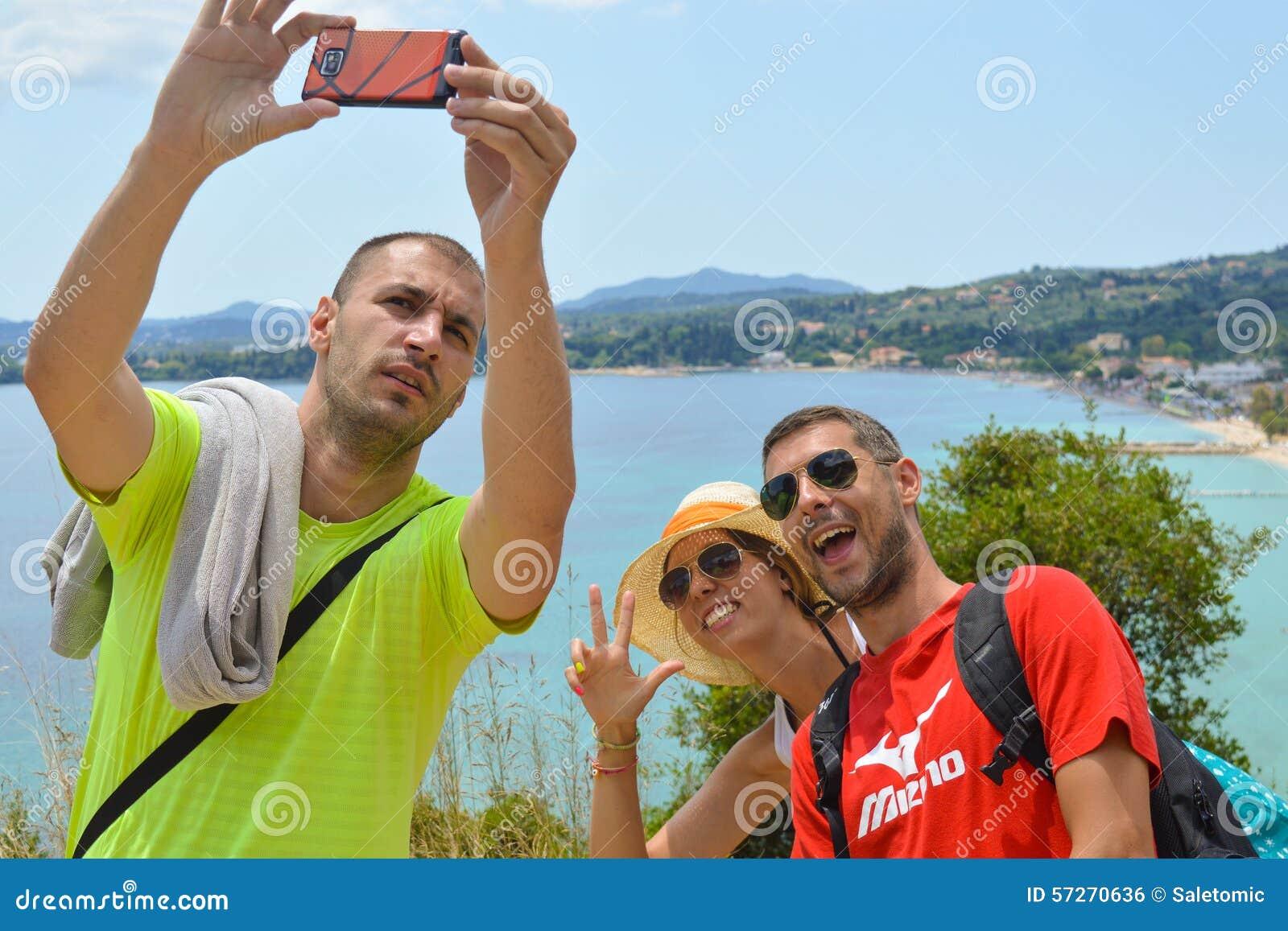 Młoda szalona grupa przyjaciele z nowożytnym mobilnym mądrze telefonu mak