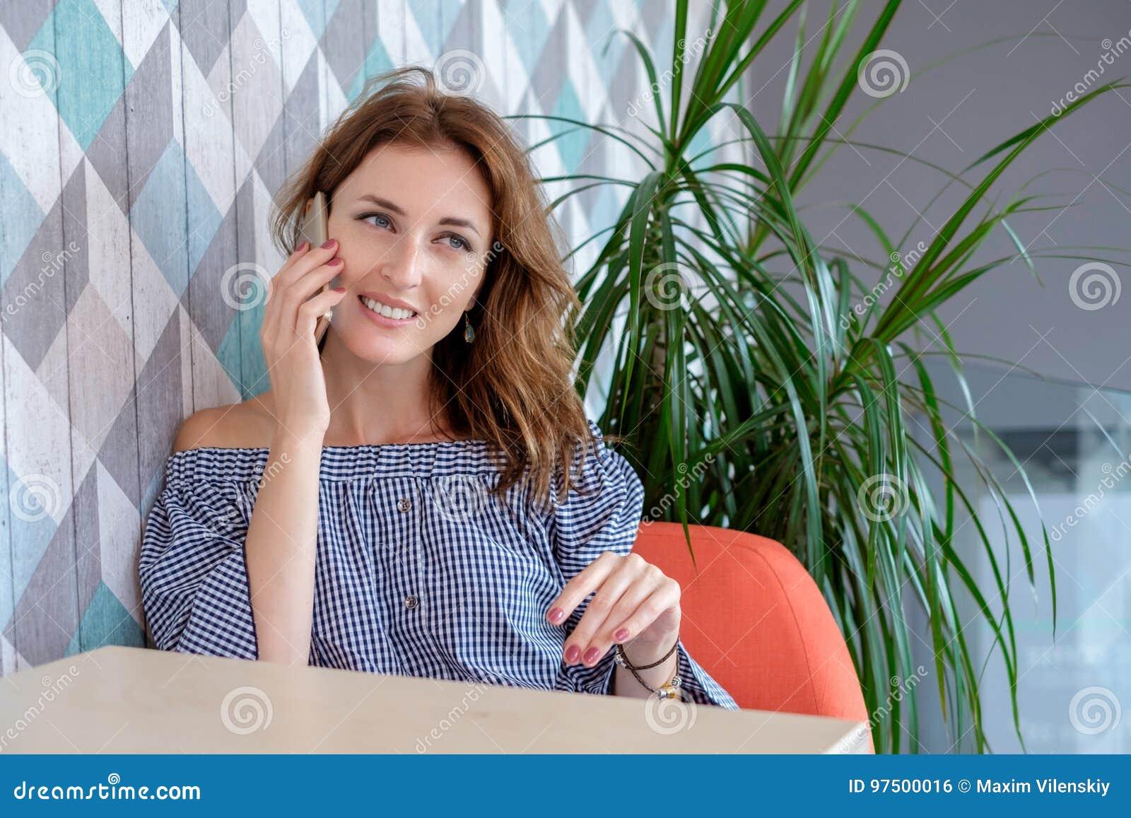 Młoda szczęśliwa kobieta opowiada na telefonie komórkowym z przyjacielem podczas gdy siedzący samotnie w nowożytnym sklep z kawą