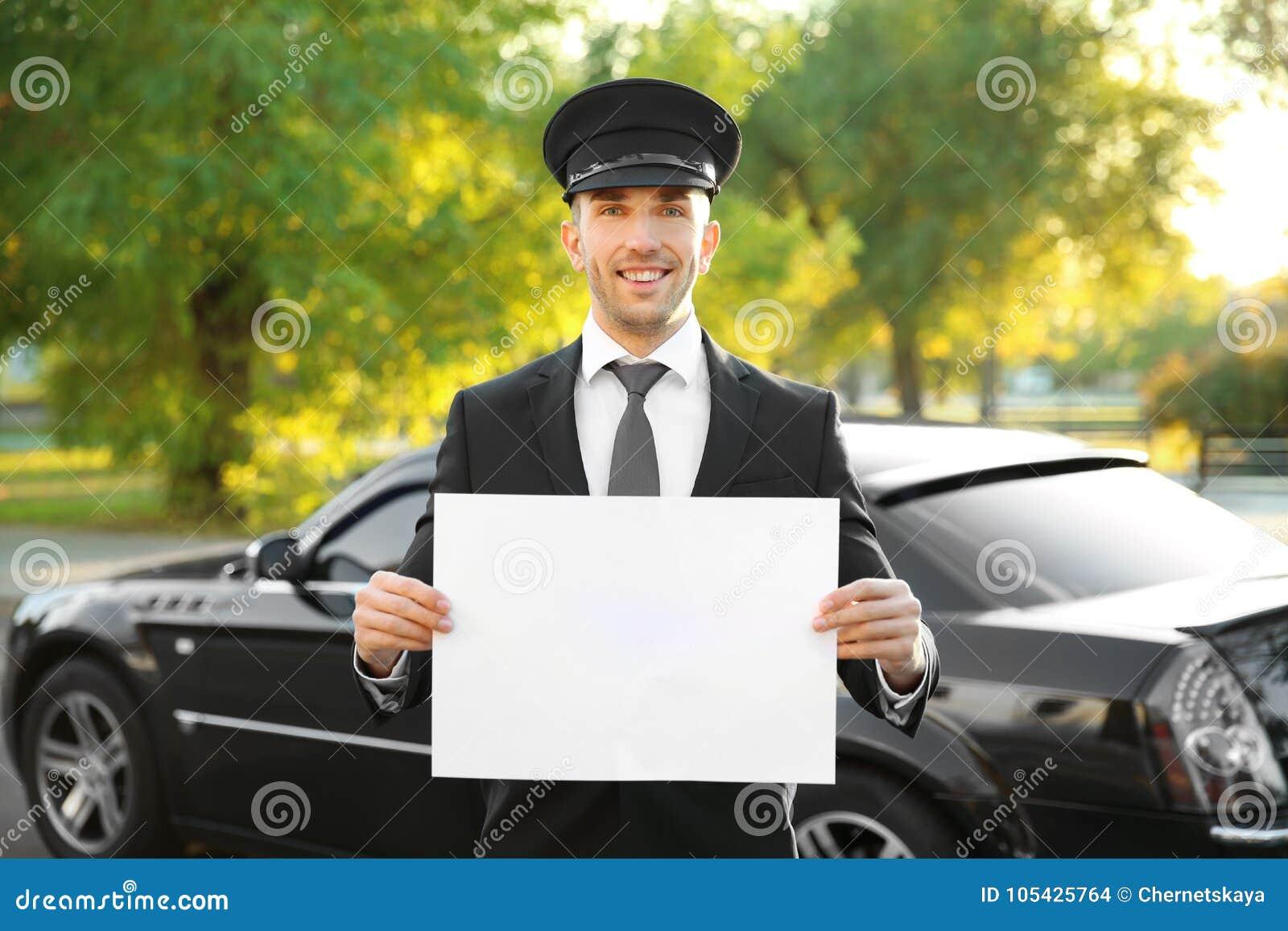 Młoda szofer pozycja z białą deską blisko luksusowego samochodu