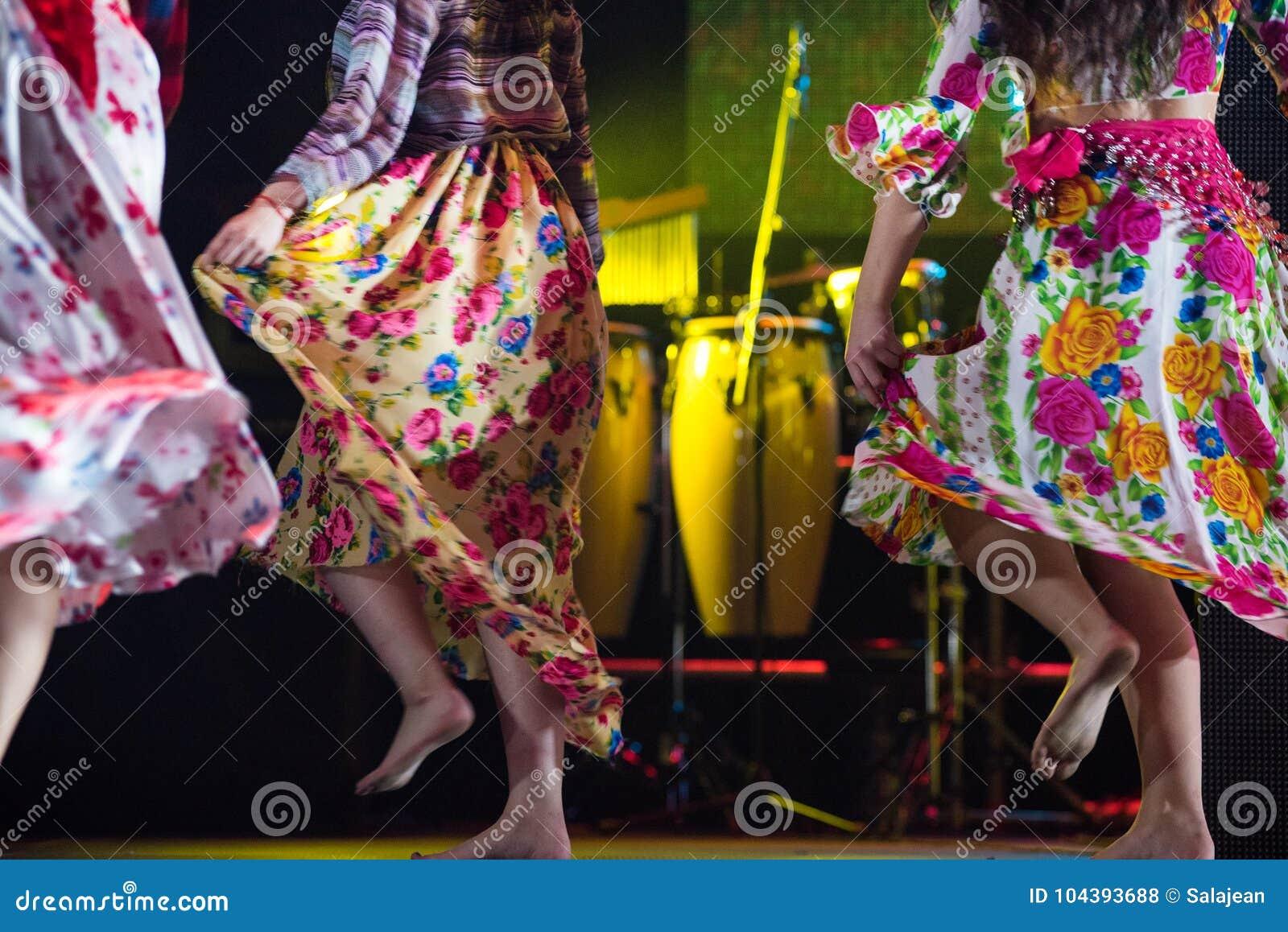 Młoda tancerz kobieta bosa w gypsy sukni tanu na scenie