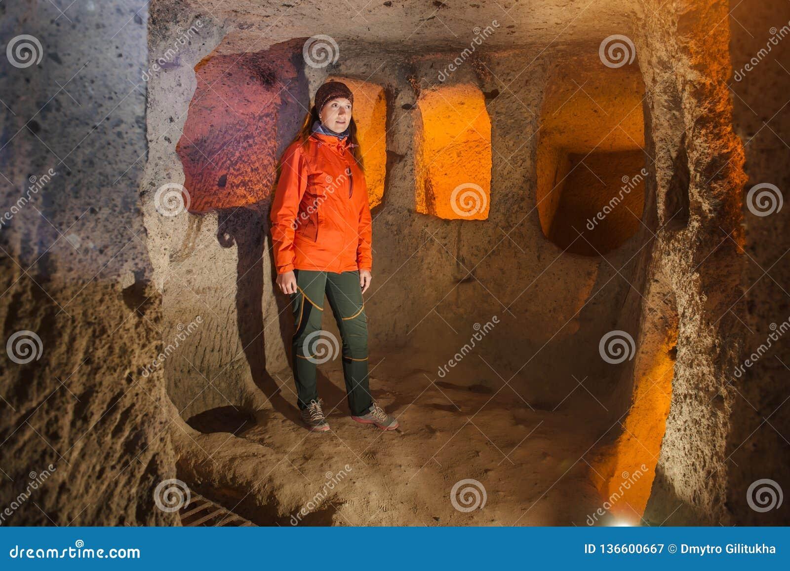 Młoda turystyczna kobieta bada antycznego Kaymakli jamy podziemnego miasto
