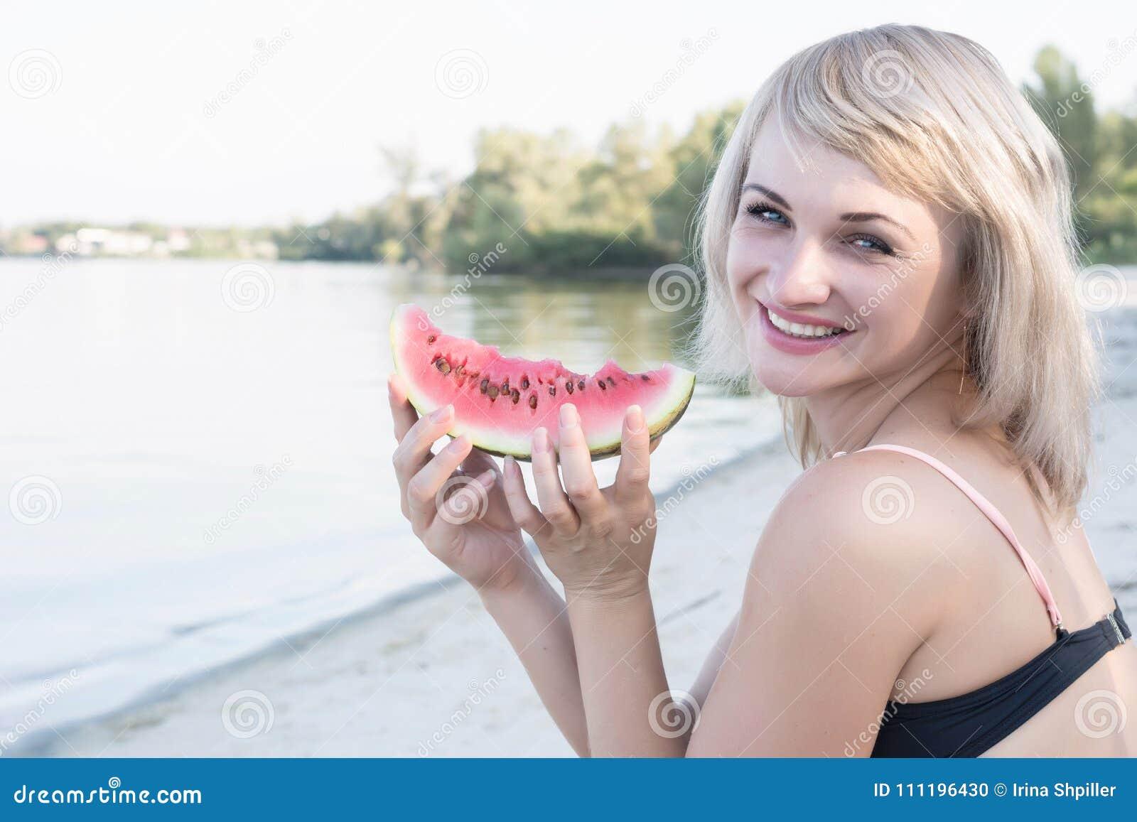 Młoda uśmiechnięta blond kobieta z kawałkiem arbuz