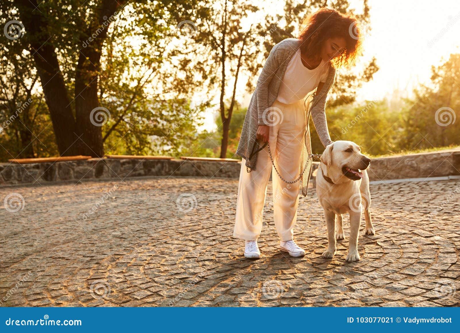Młoda uśmiechnięta dama siedzi psa w parku i ściska w przypadkowych ubraniach
