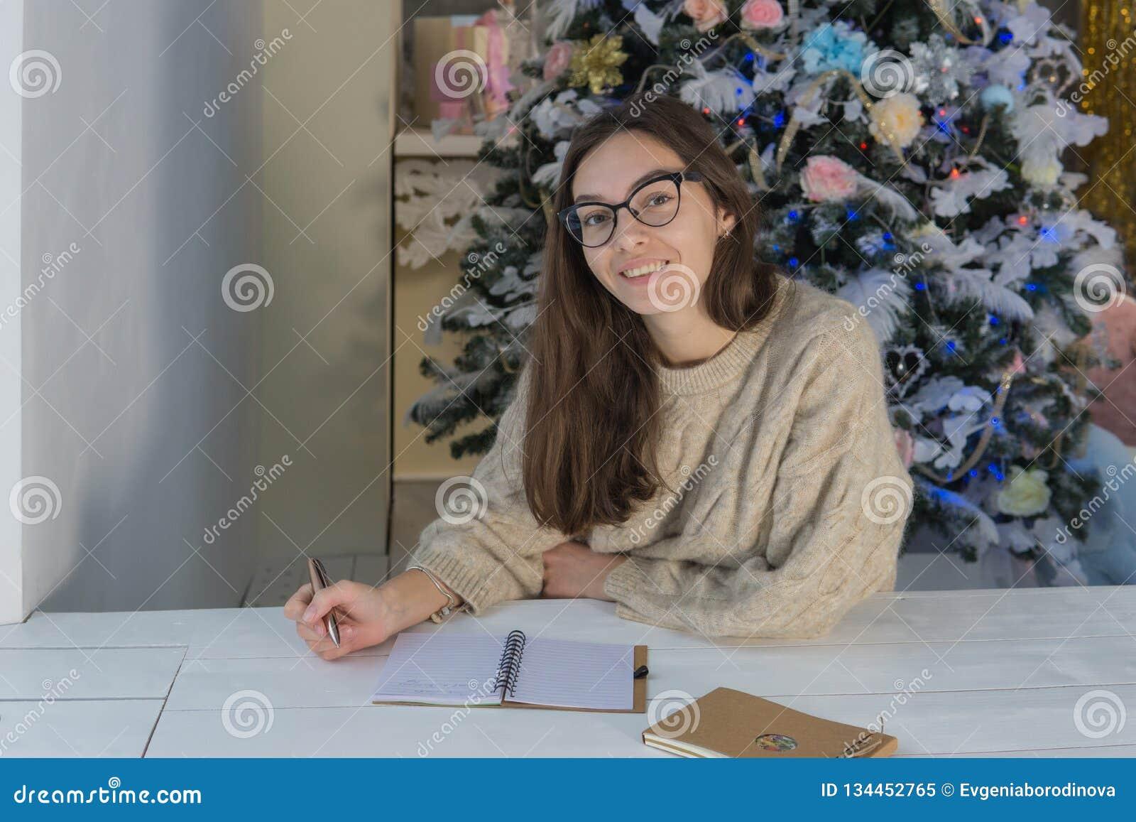 Młoda uśmiechnięta kobieta patrzeje ono uśmiecha się i kamerę obok drzewa
