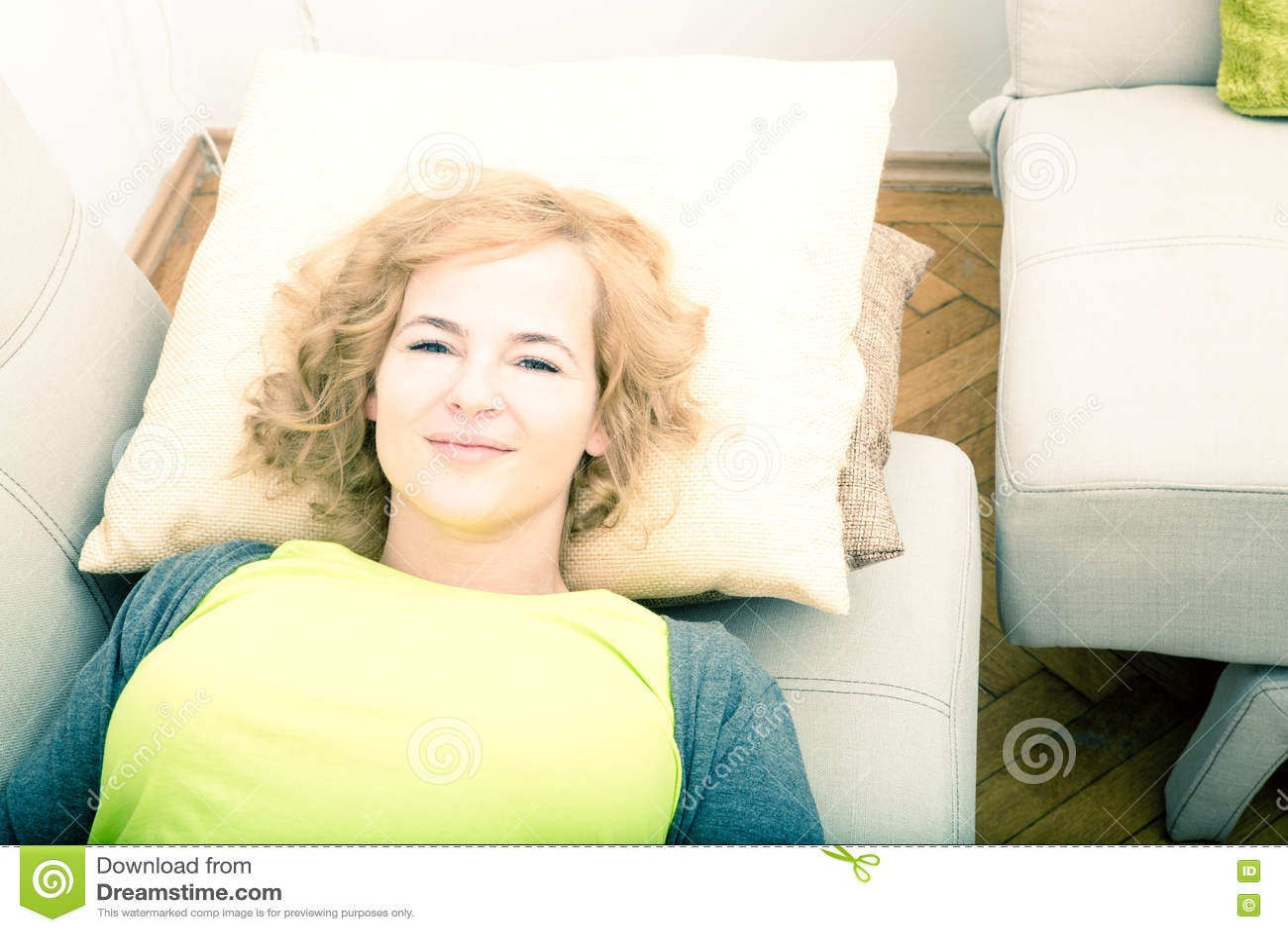 Młoda uśmiechnięta kobieta relaksuje na kanapie